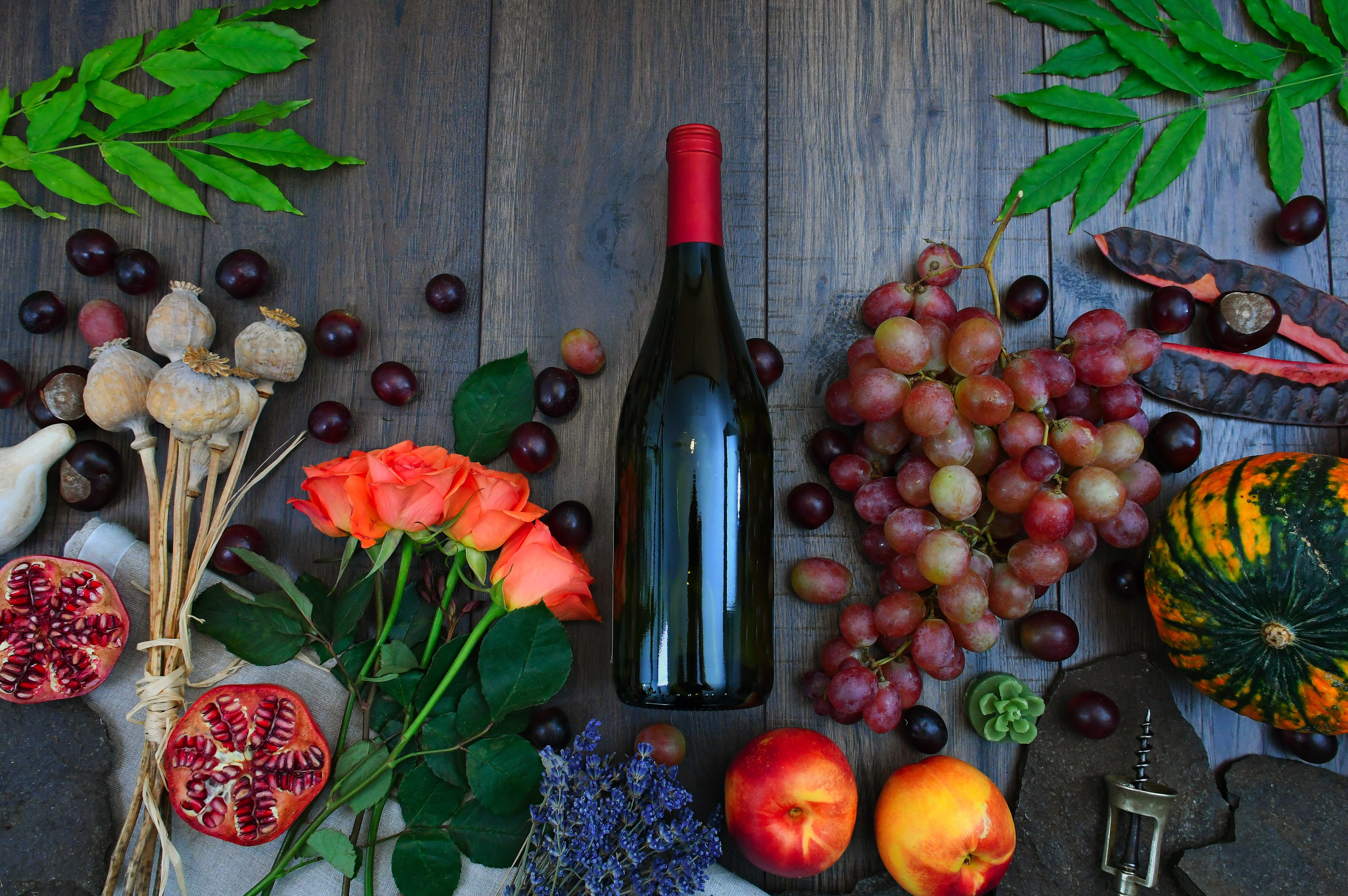 Wine Bottle Beside Grapes, Roses and Several Fruits on Brown Wooden Surface