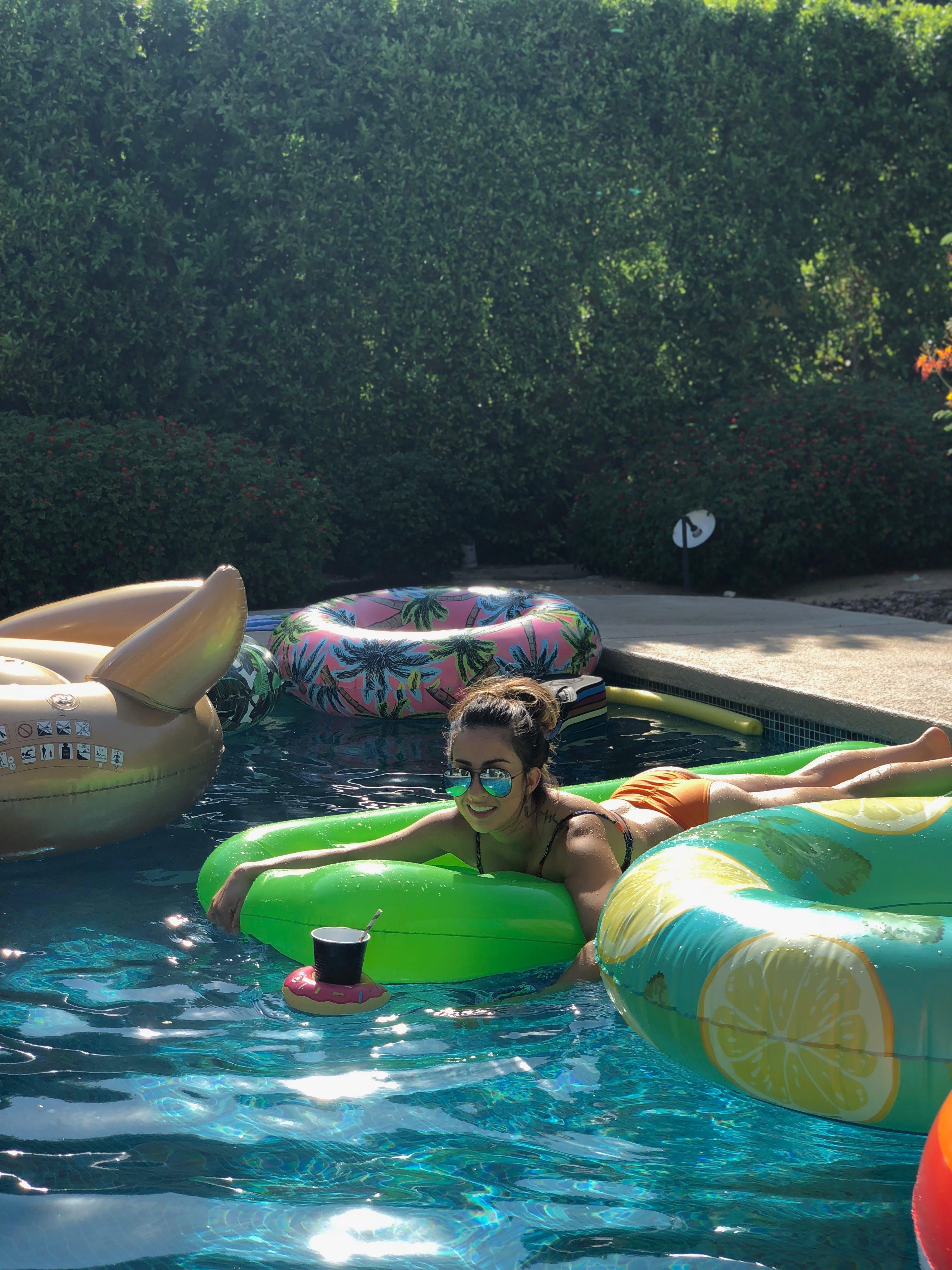Woman Wearing Orange Bikini Lying on Green Inflatable Bed Inside Pool a Day
