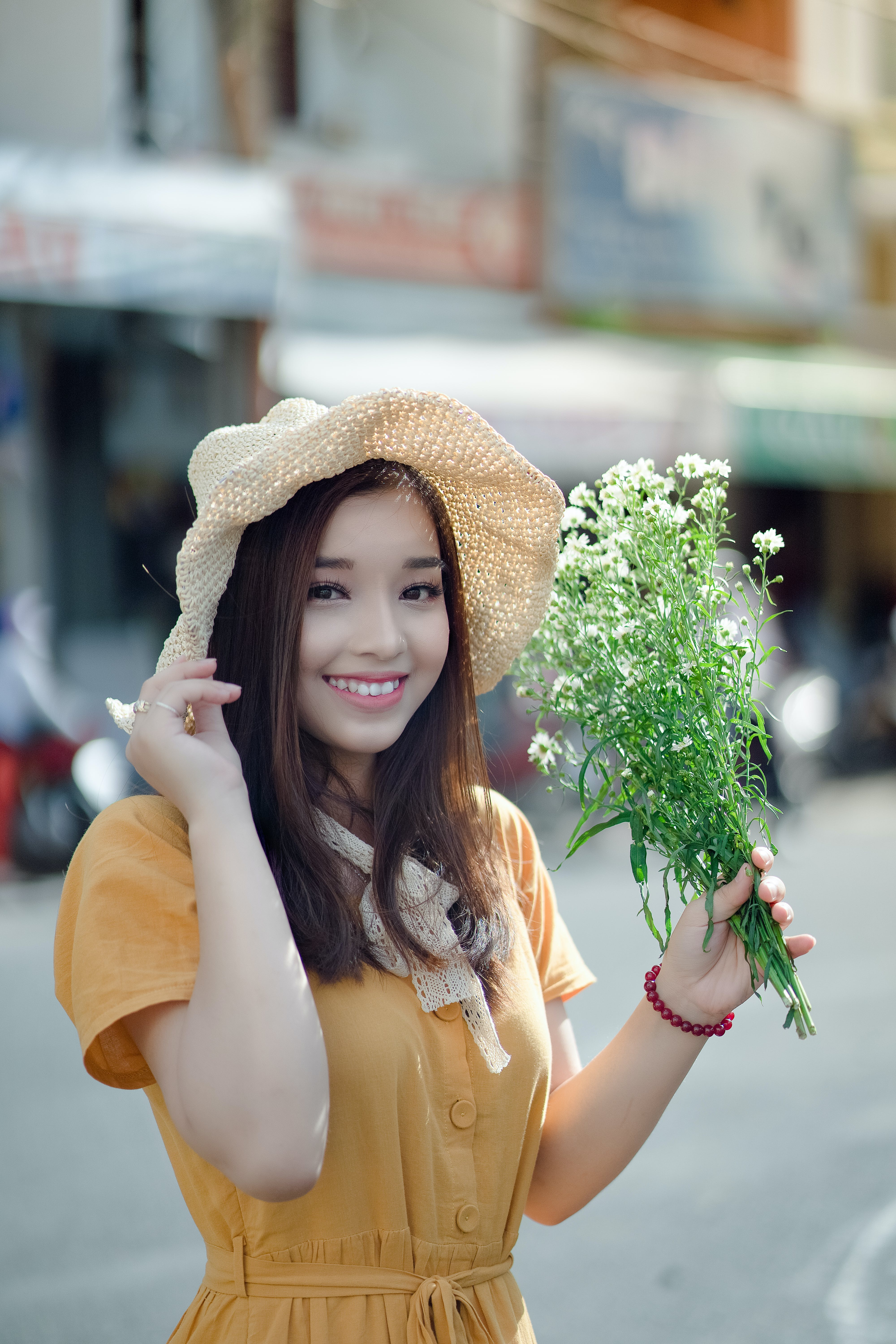 Smiling Woman Wearing Hat Holding White Petaled Flower Standing on Street