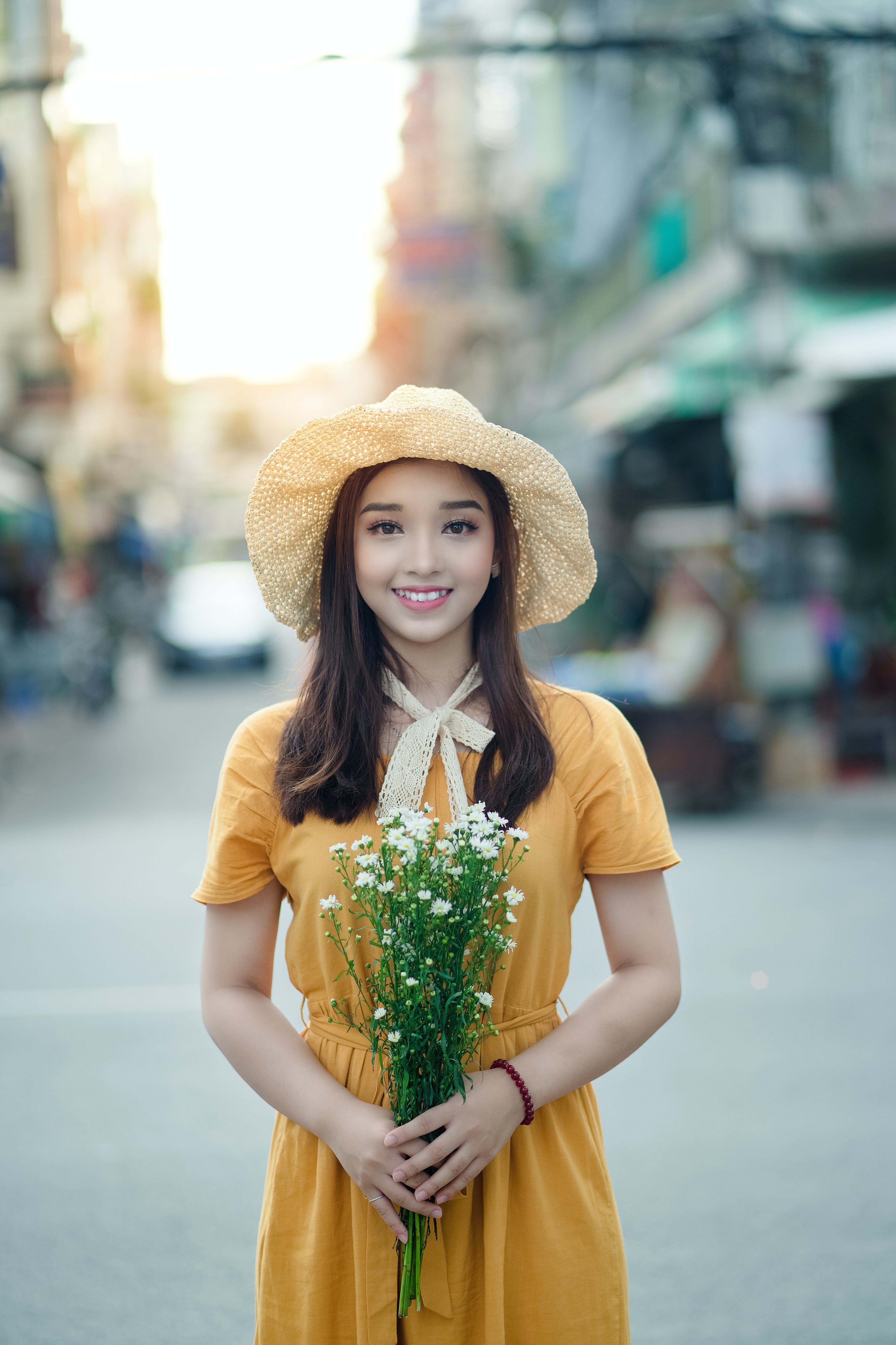 Selective Focus Photography Of Woman Holding Flowers