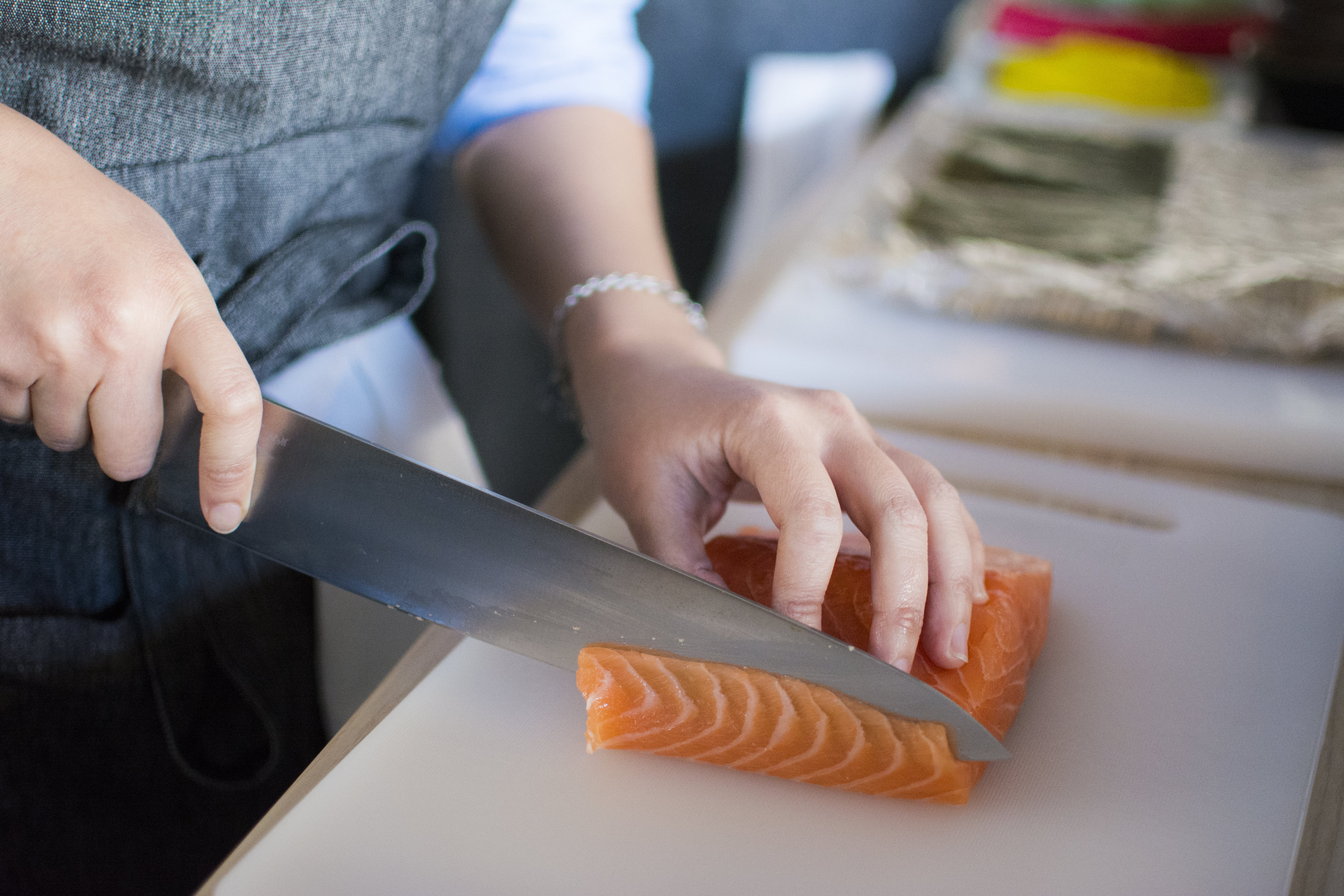 Person Slicing Meat On White Chopping Board