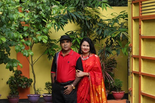 Man Standing Beside Smiling Woman Near Potted Green Leafed Plants
