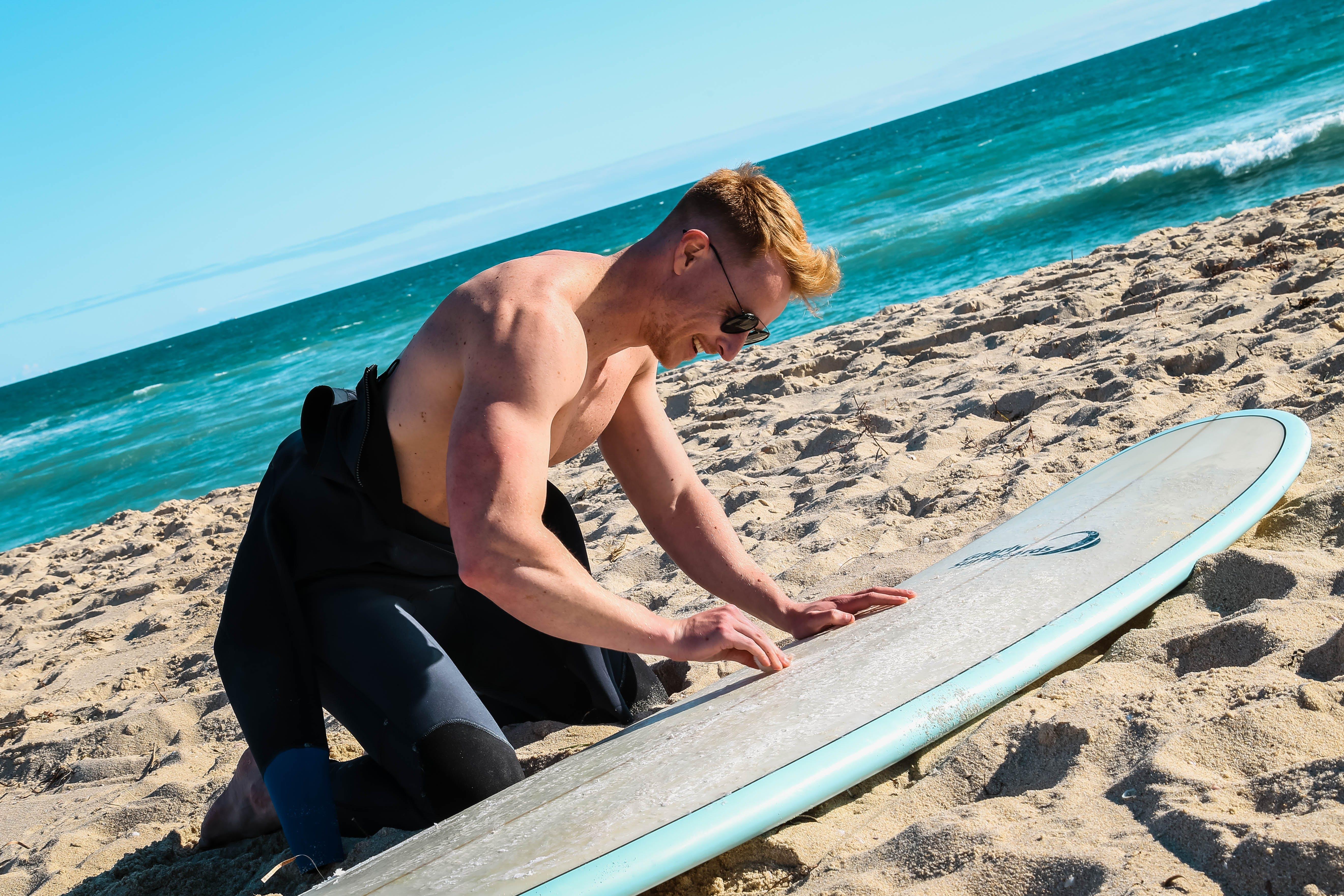 Man Waxing Surfboard on Beach