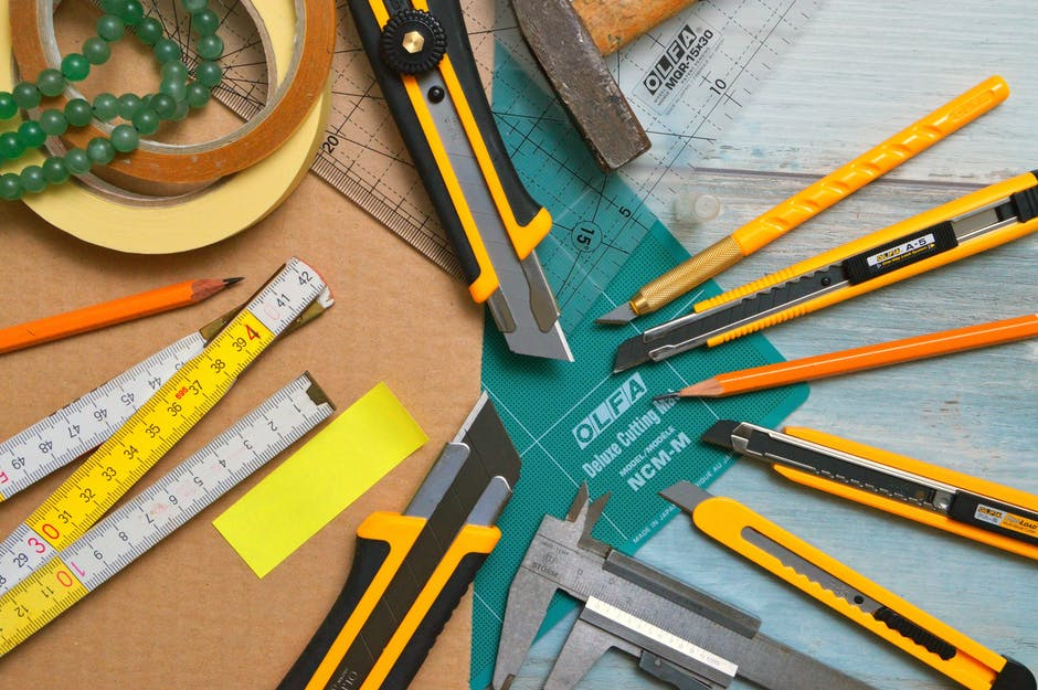 Assorted type and size utility cutters on clear and green olfa measuring tool near adhesive tape rol...