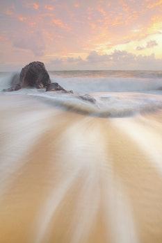 Brown Sand Beside Brown Rock during Daytime