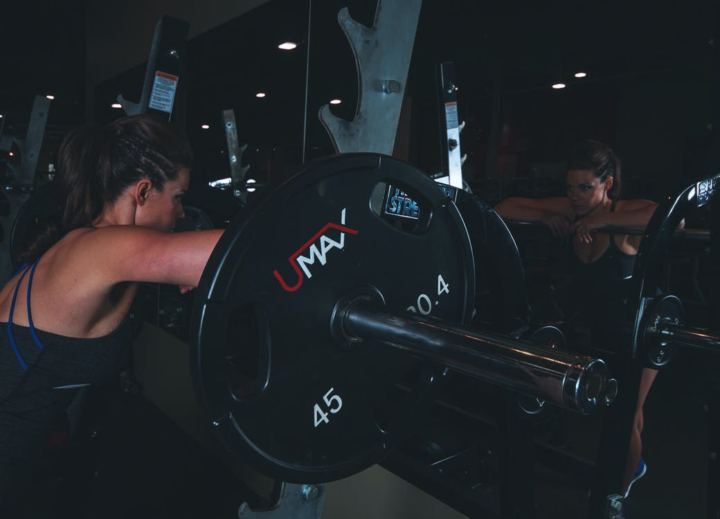 Woman Leaning on Black Barbell in Front Mirror
