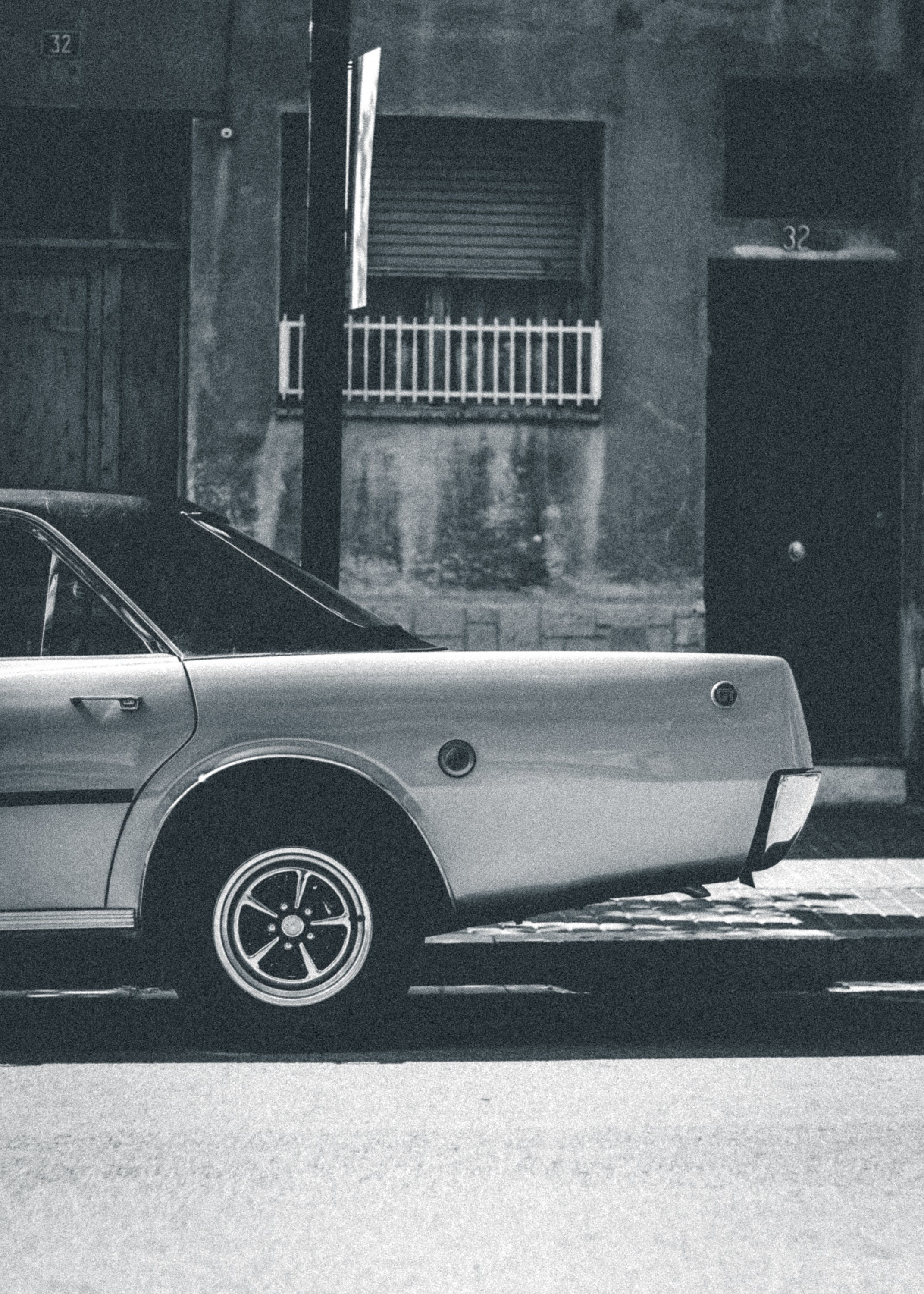 Grayscale Photography Of Sedan On Roadside