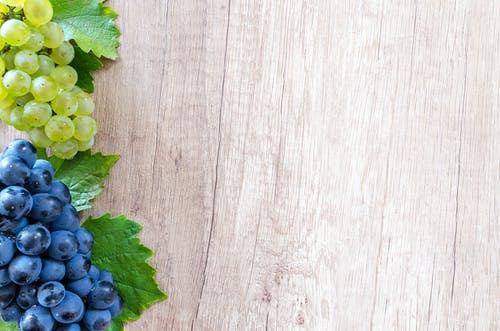 Grapes on Brown Wooden Surface