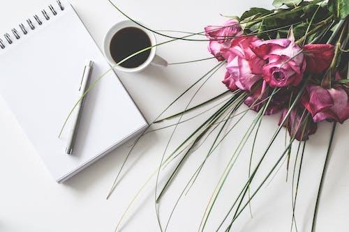 Bukiet Czerwonych Róż Na Białej Powierzchni Obok Książki Wiosennej Z Długopisem I Filiżanką Kawy