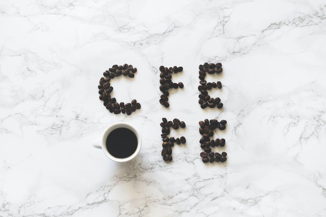 Coffee Beans and White Ceramic Mug With Black Liquid