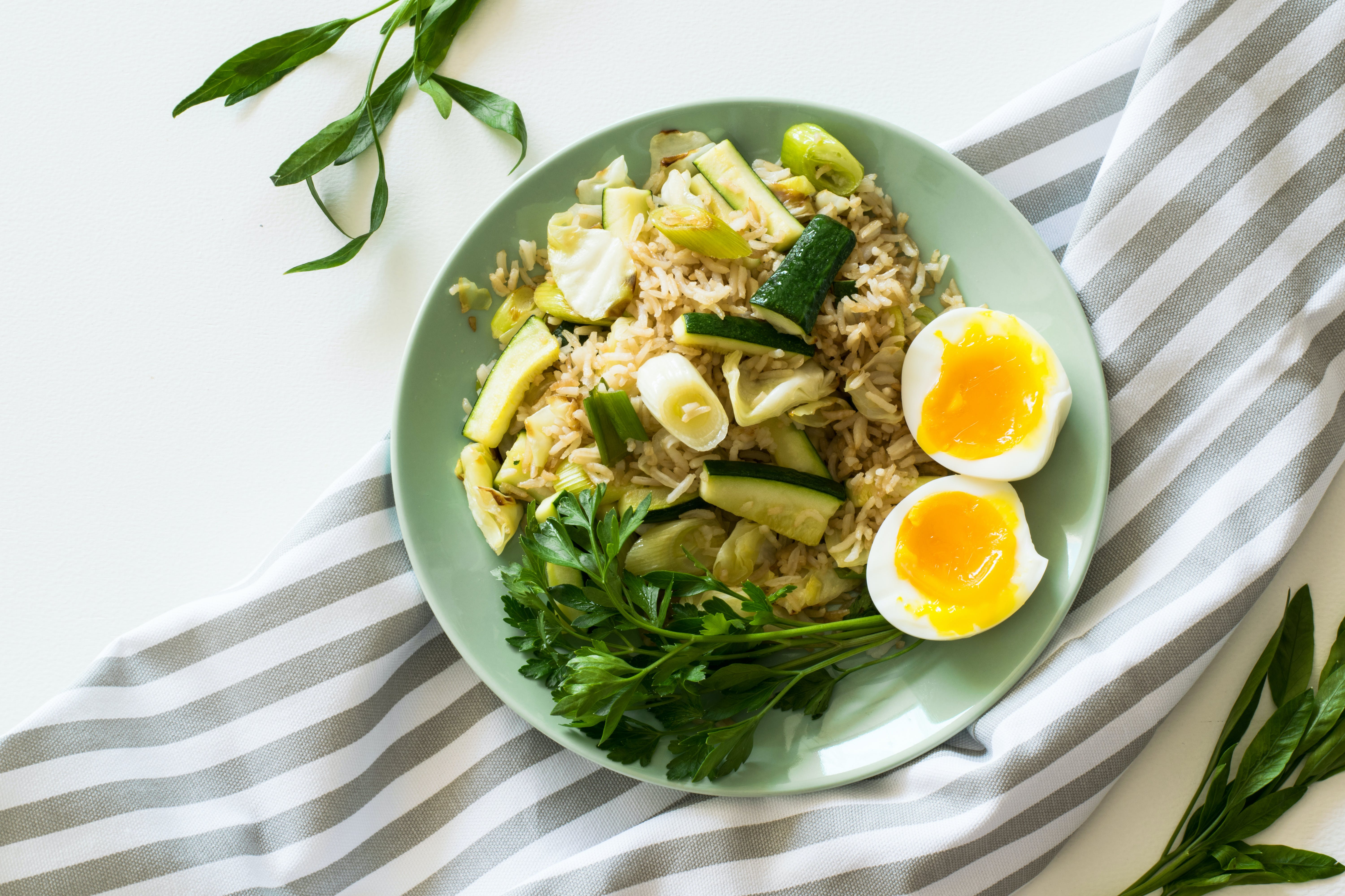 Fried Rice With Poached Egg, Zucchini, And Celery on Round Green Ceramic Plate