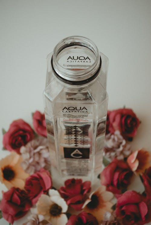 Aqua Bottle Surrounded by Flowers