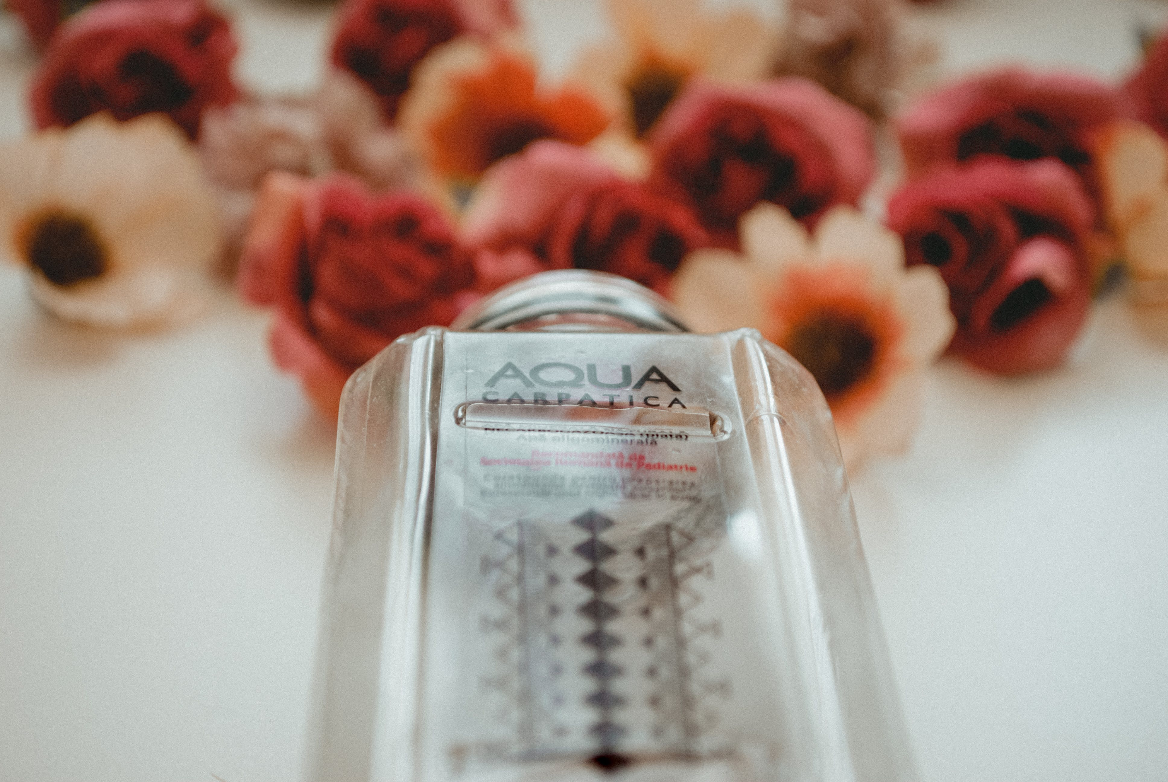 Aqua Carpalica Bottle Near Flowers on White Surface