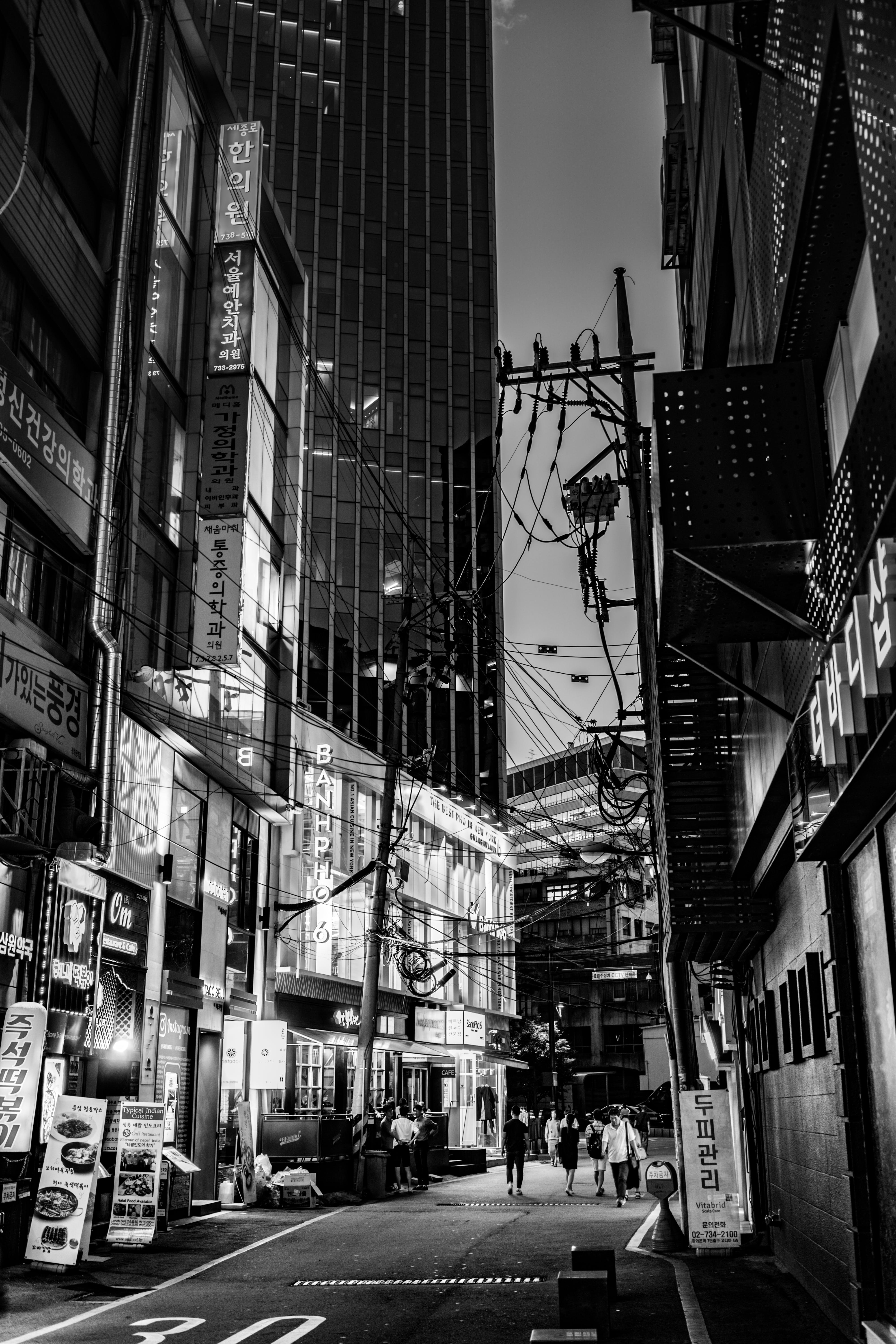 Grayscale Photo of Buildings and Roads at Night