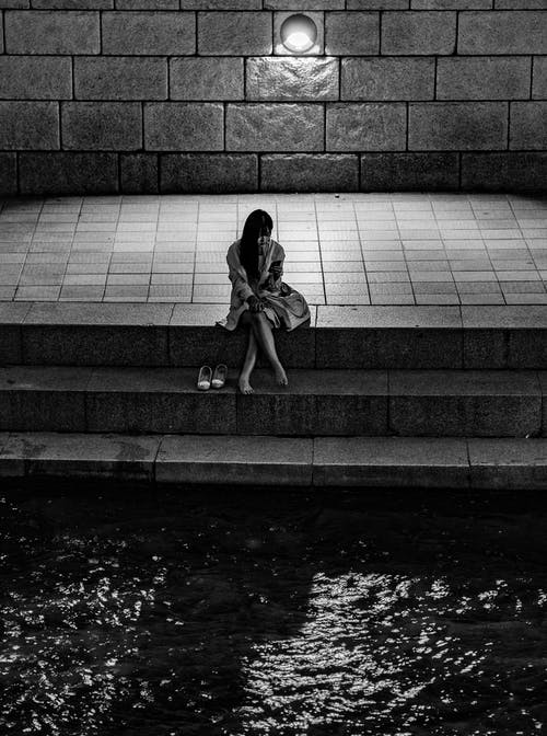 Grayscale Photo of Woman Sitting on Stair Near Concrete Wall