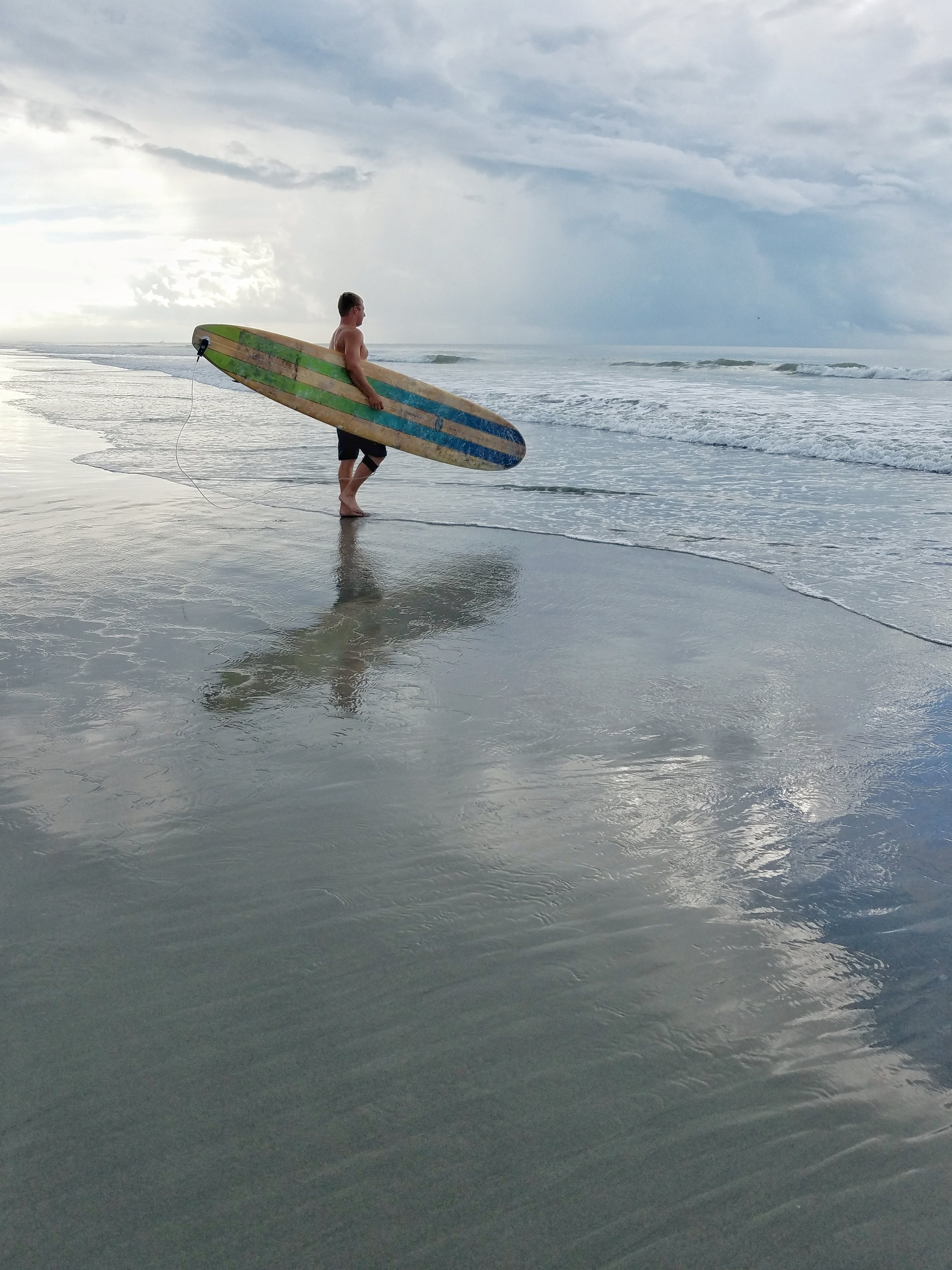 Man Holding Surfboard While Staring At The Ocean