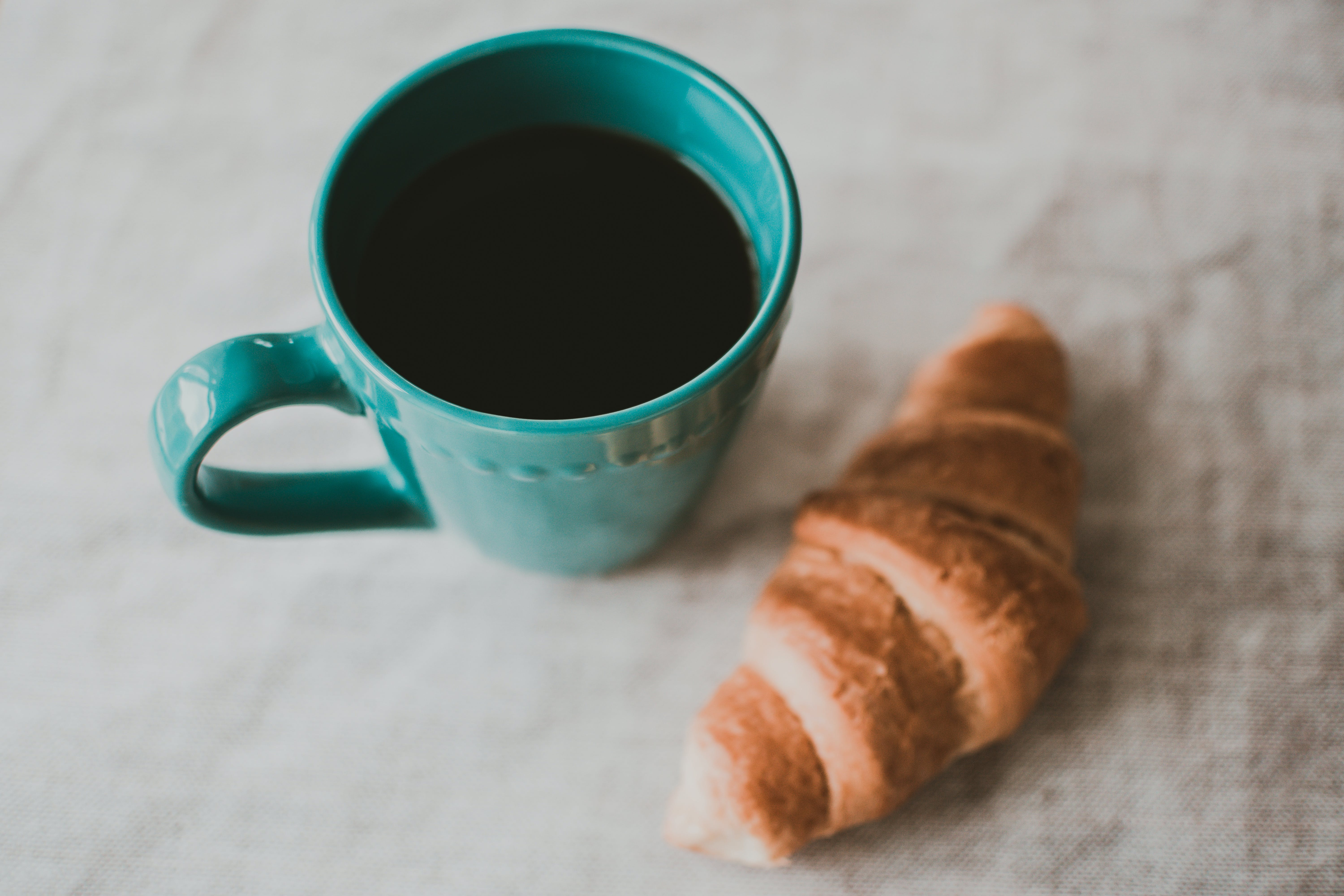 Teal Ceramic Mug Filled With Coffee Near Baked Bread