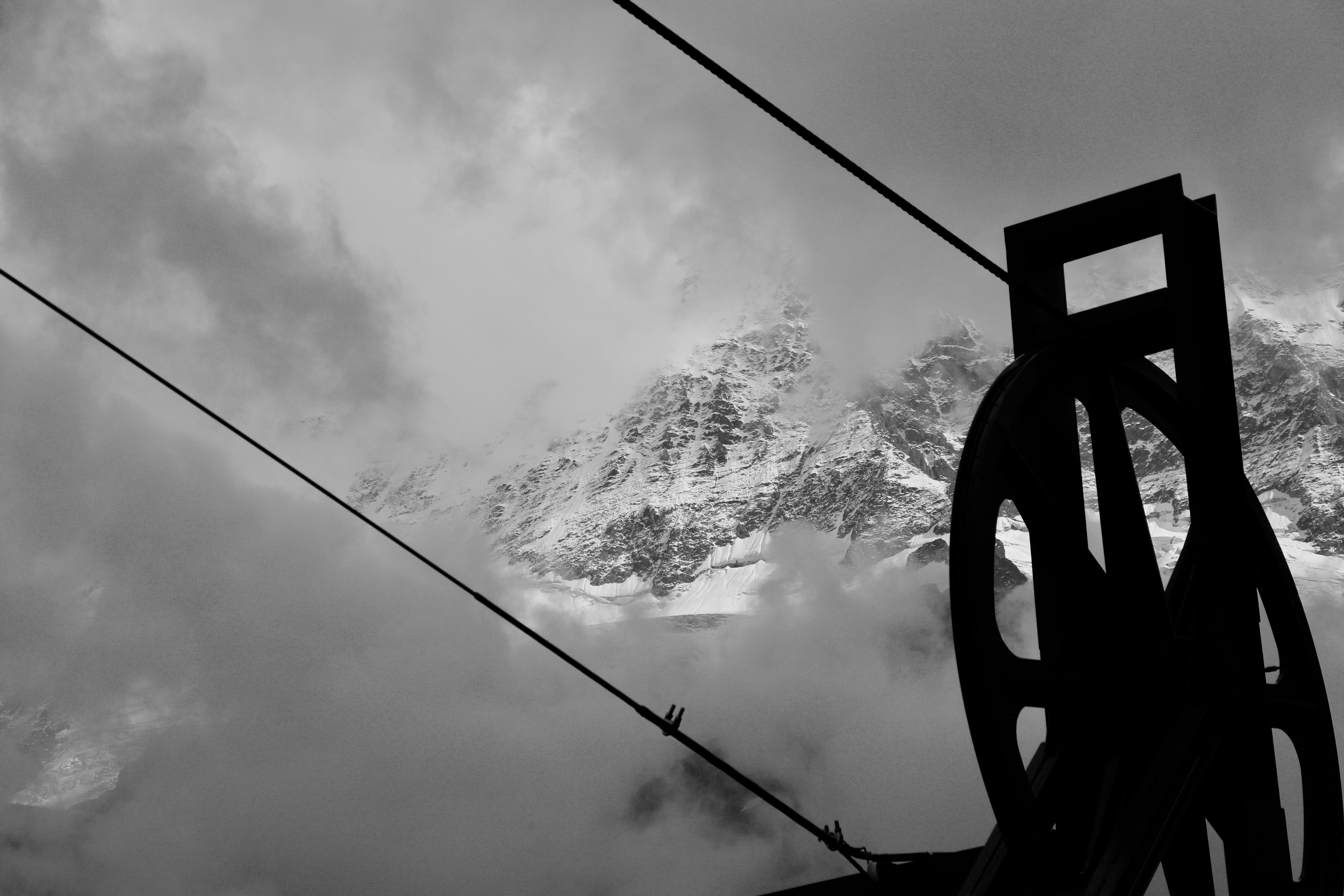 Grayscale Photography of Pulley Near Mountain