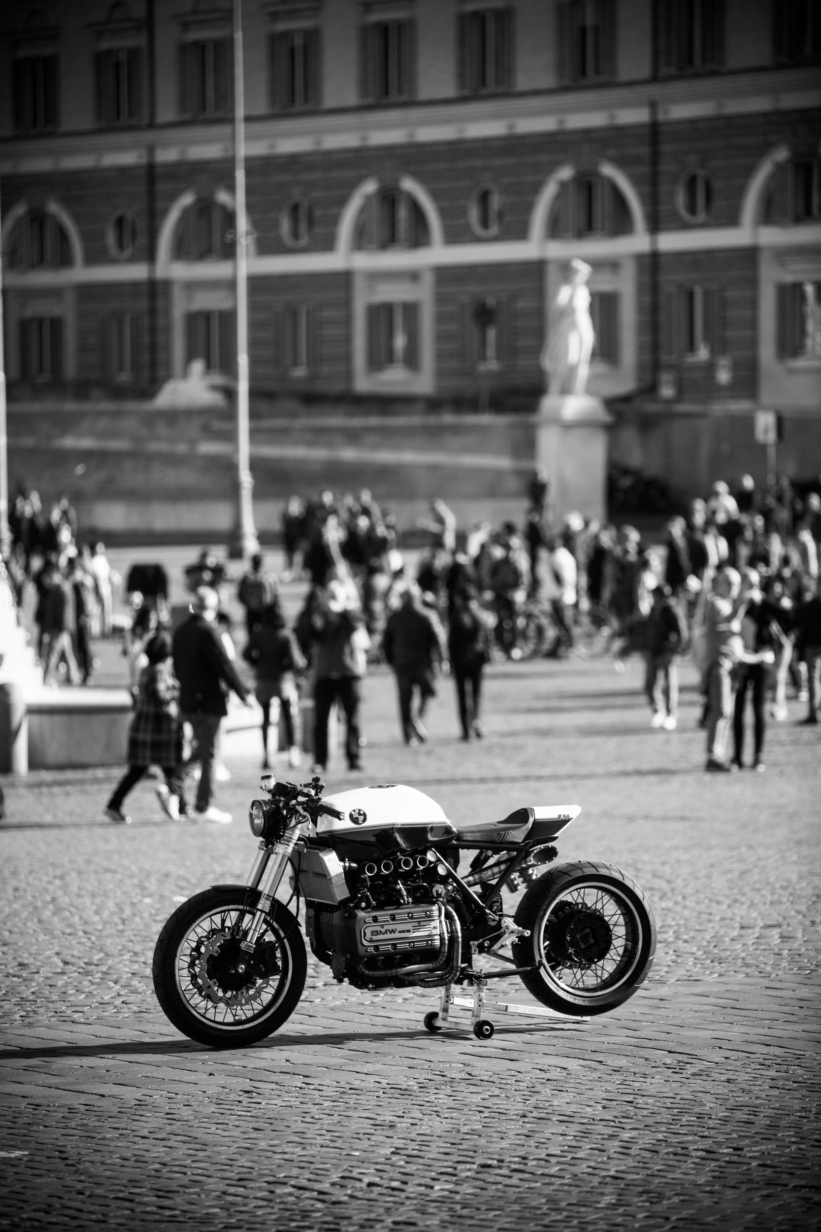 Grayscale Photo of Sports Bike Parked Near People