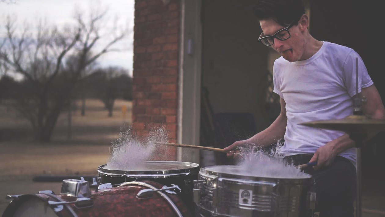 Person Playing on Drums during Daytime