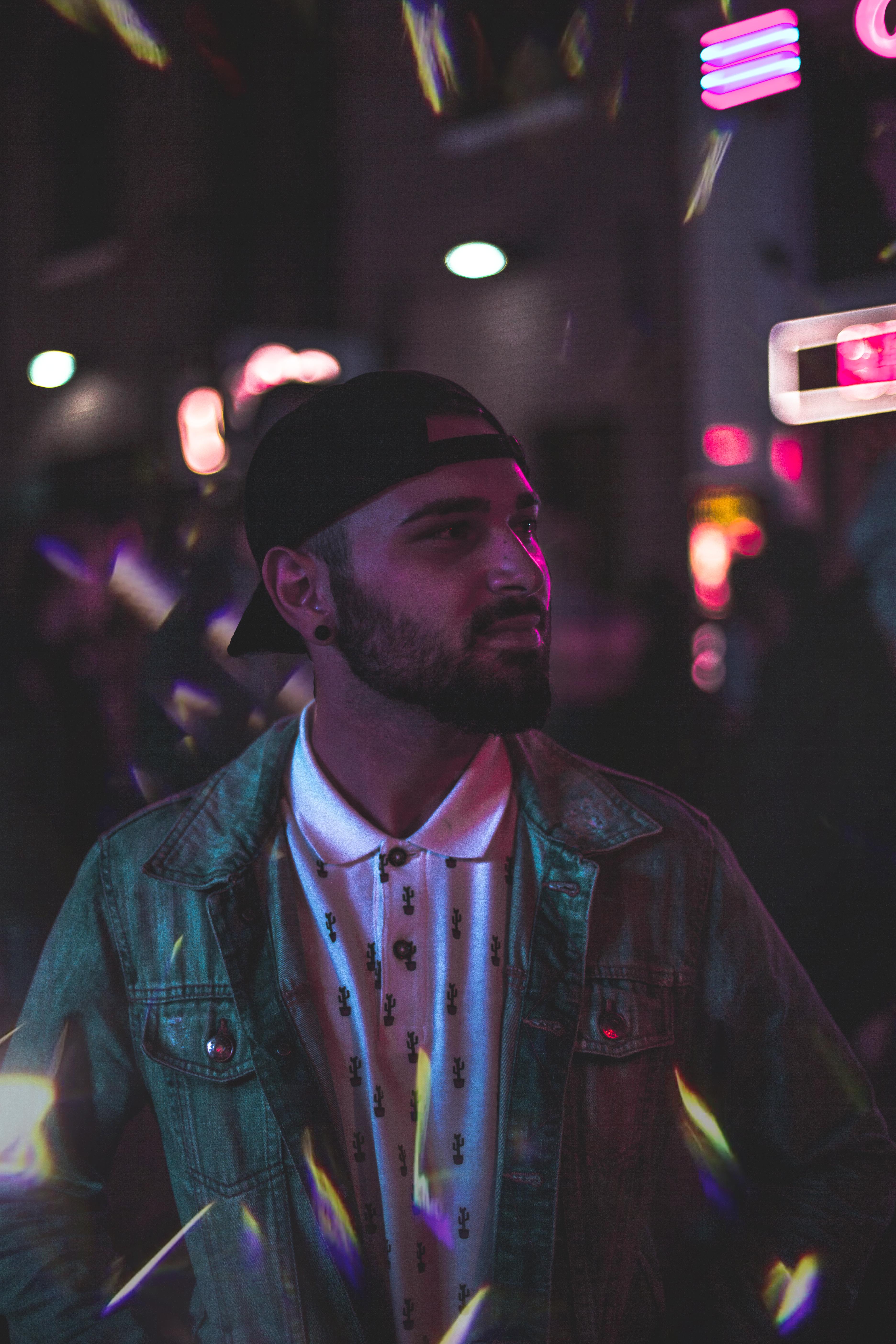 Man Wearing Gray Denim Jacket and Black Cap at Night