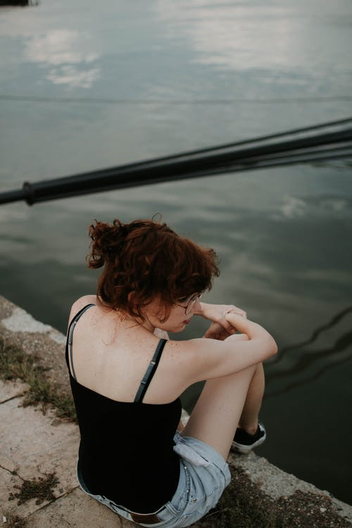 Woman Wearing Black Cami-top Sitting on Concrete Surface Near Body of Water