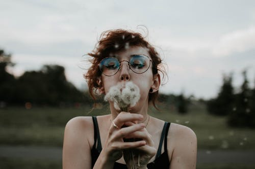 Selective Focus Photography of Woman Blowing Dandelion Flower