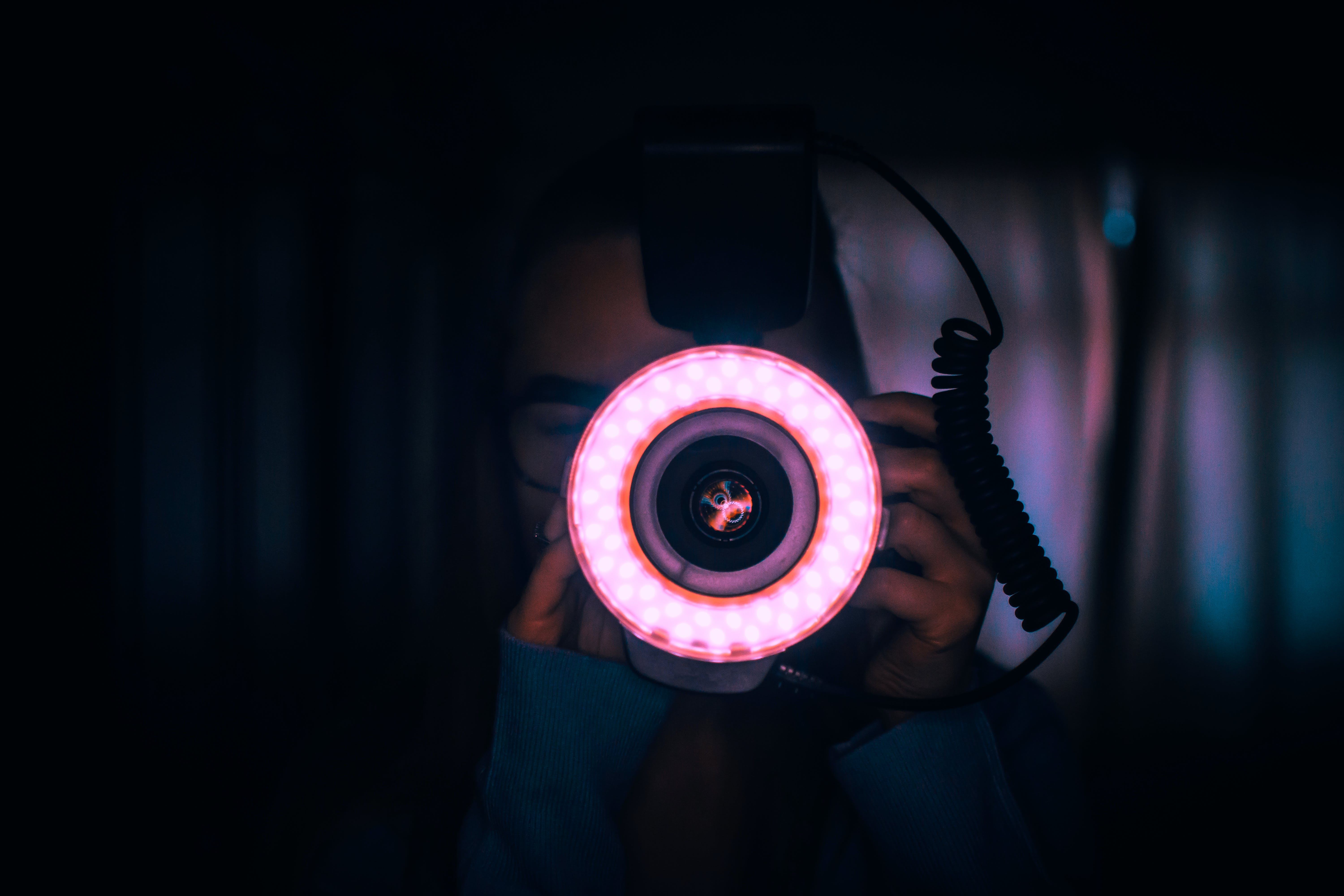 Person Holding Camera With Red Lights on Lens