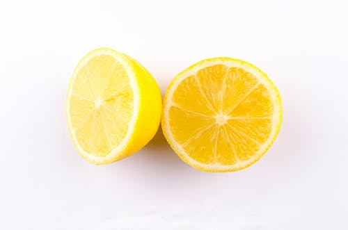 Close-up Photo of Sliced Yellow Lemon on White Surface