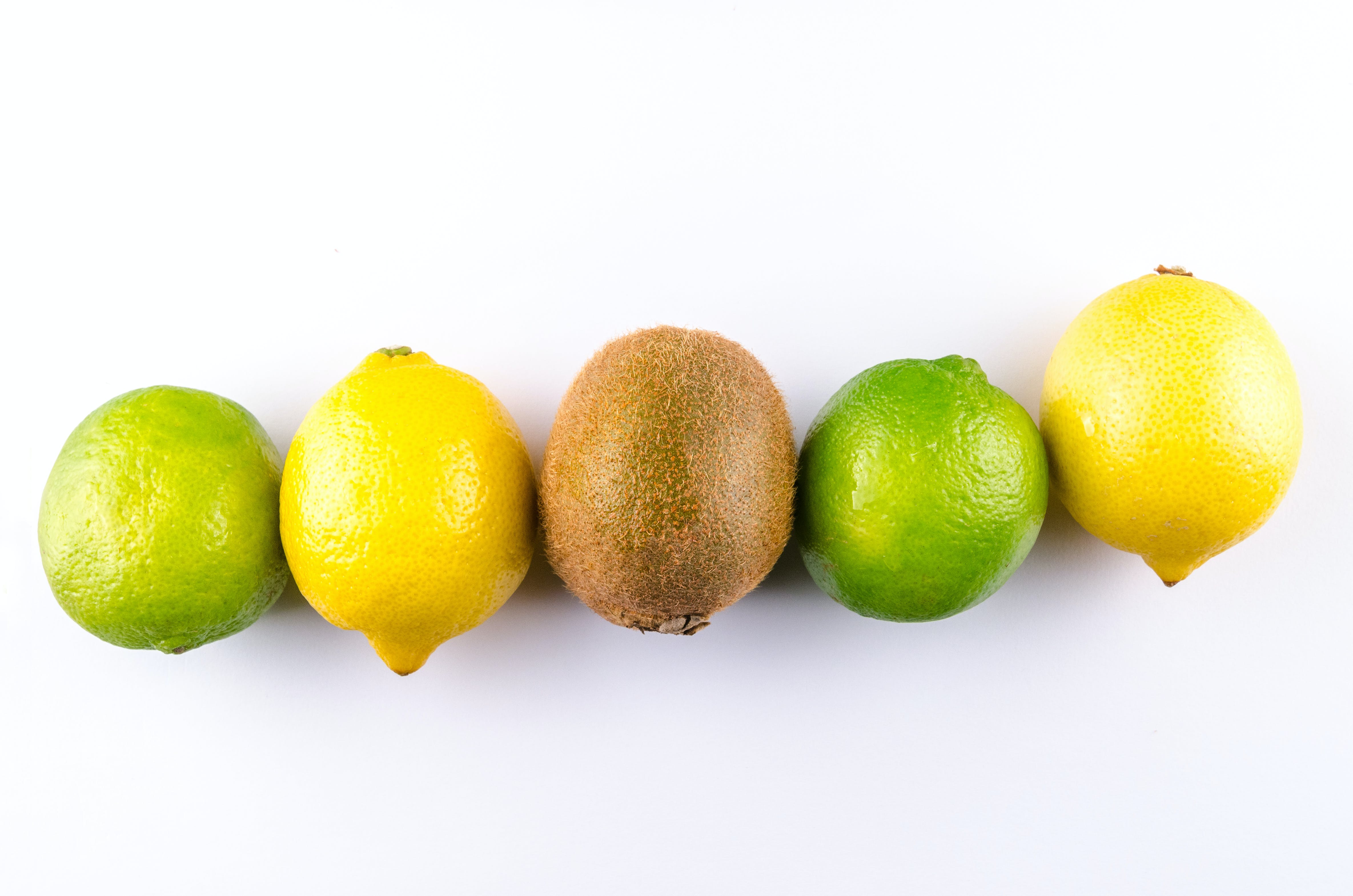 Flat Lay Photo of Two Lemon, Two Limes, and One Kiwi