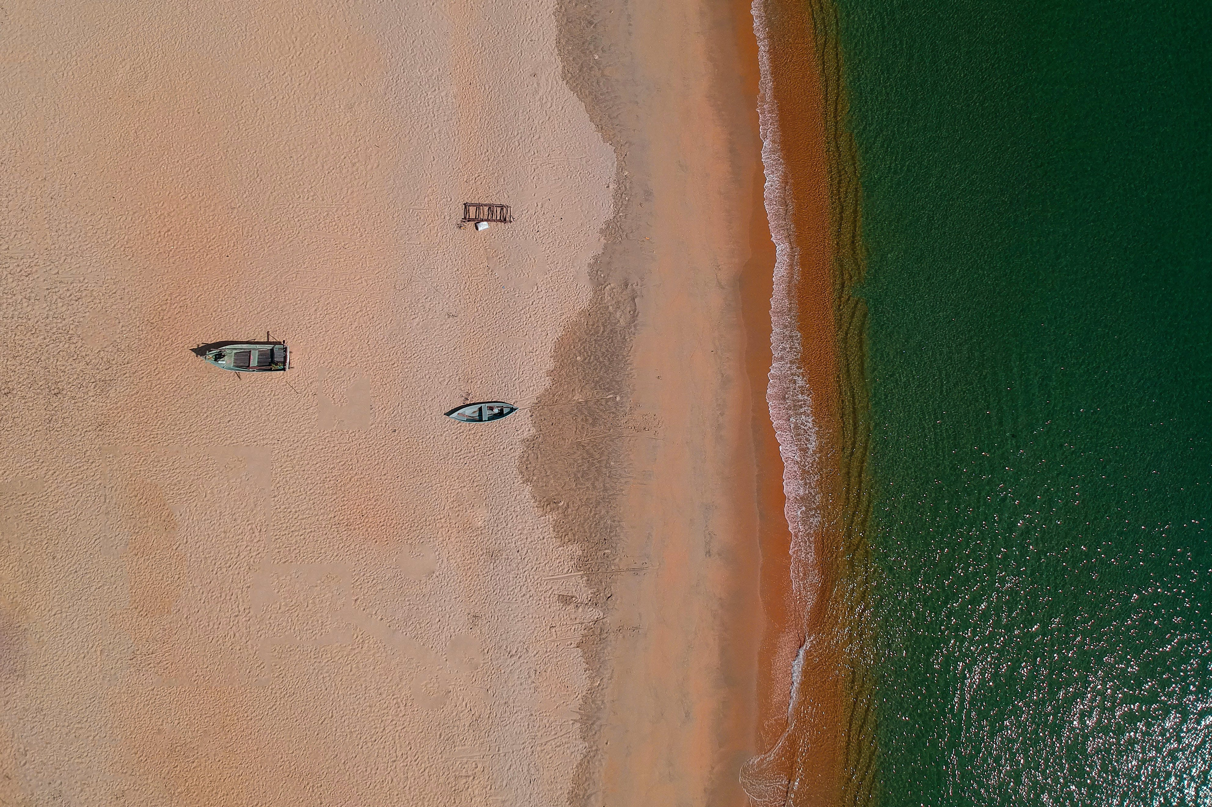 Aerial Photography of Two Gray Wooden Boats on Sand Front of Sea