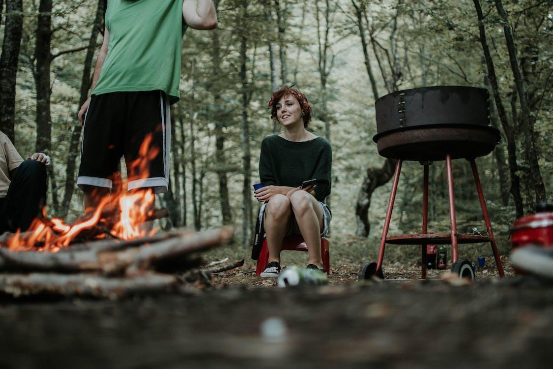 Man and Woman Gathering Around a Bonfire
