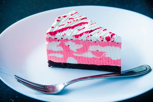 Sliced White and Pink Icing Covered Cake on White Plate With Silver-colored Fork