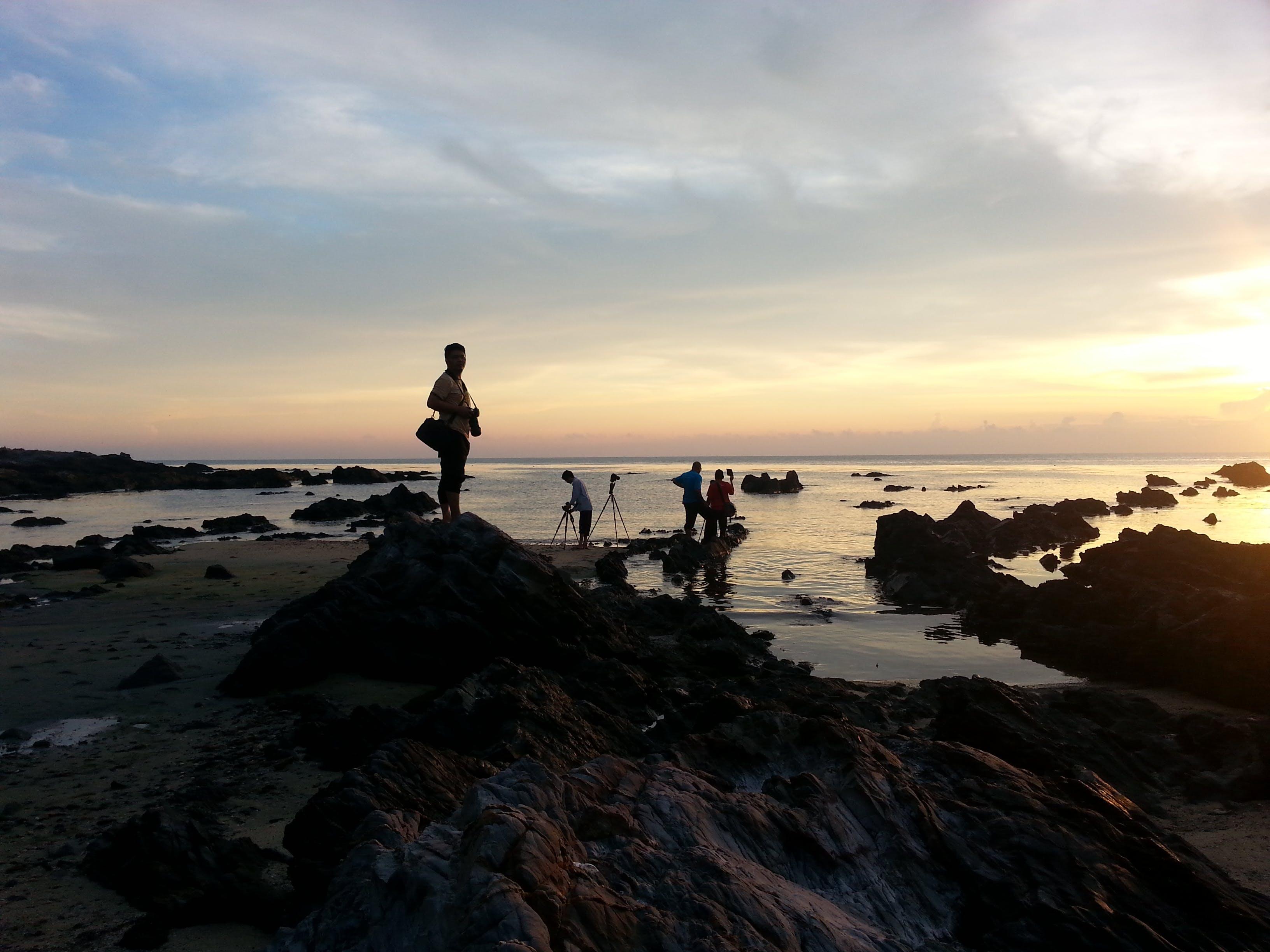 Silhouette of People on Seashore Under Gray Sky