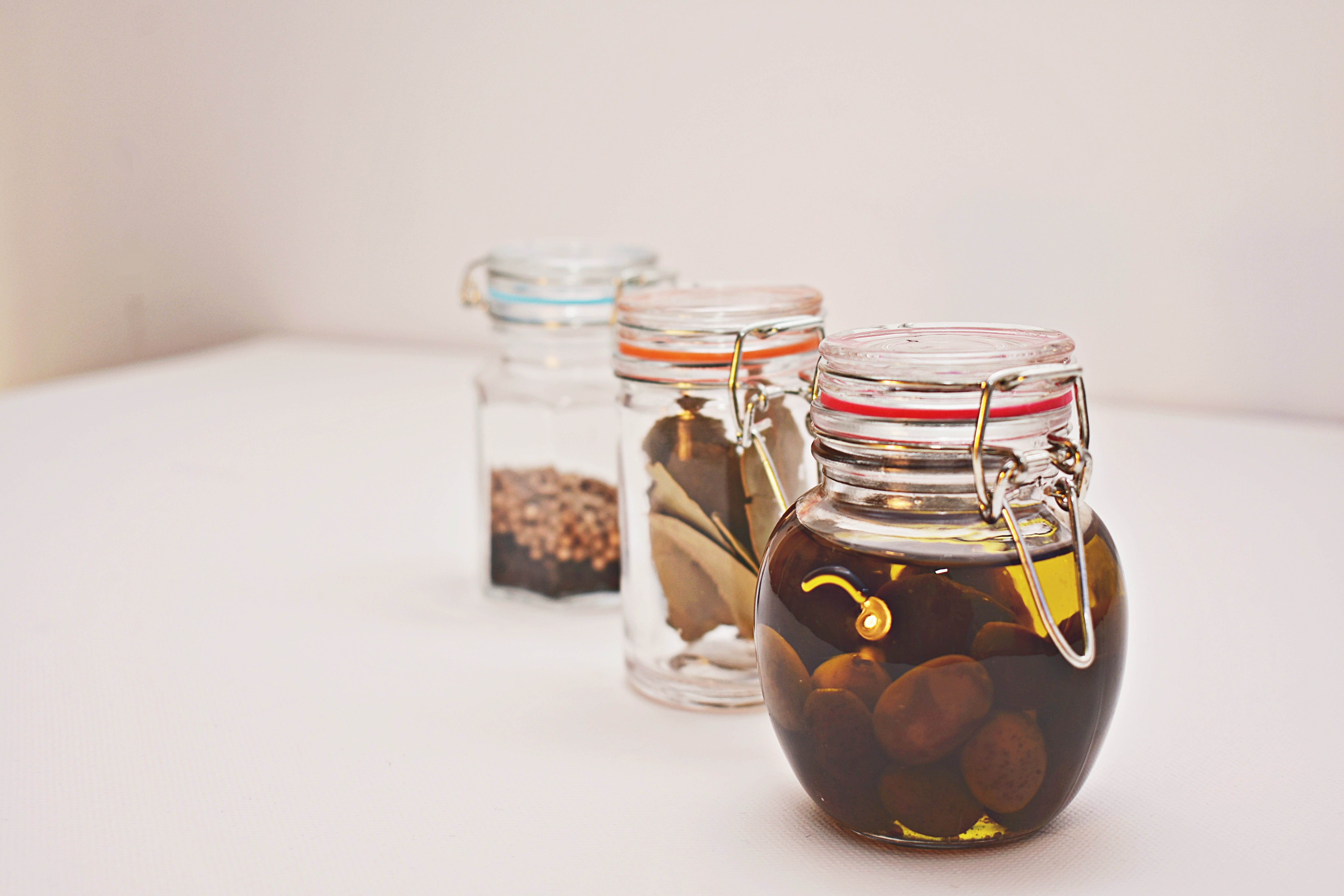 Three Clear Glass Jars on White Surface