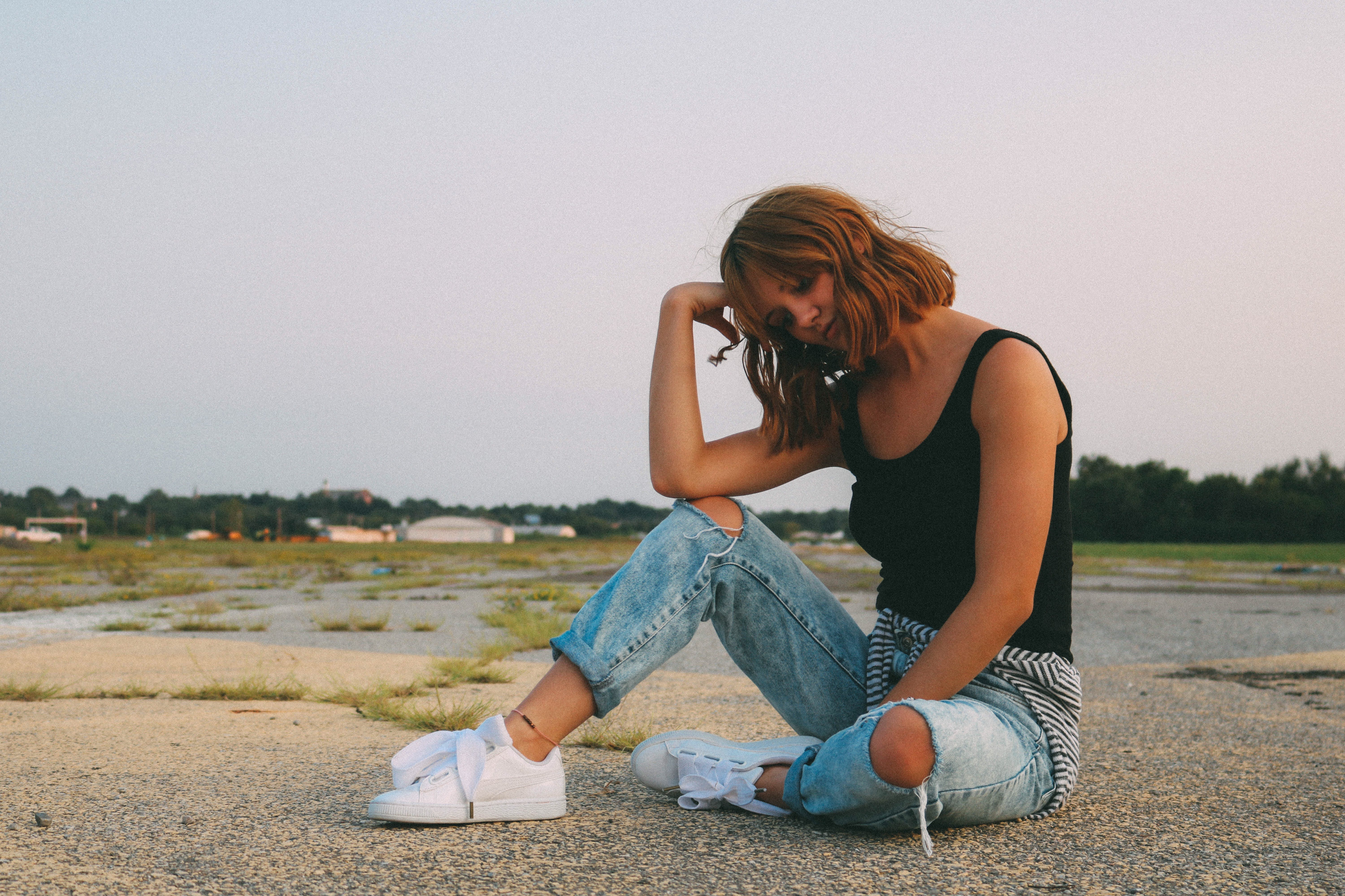 Woman Wearing Black Tank Top and Distressed Blue Denim Jeans Sits on Ground