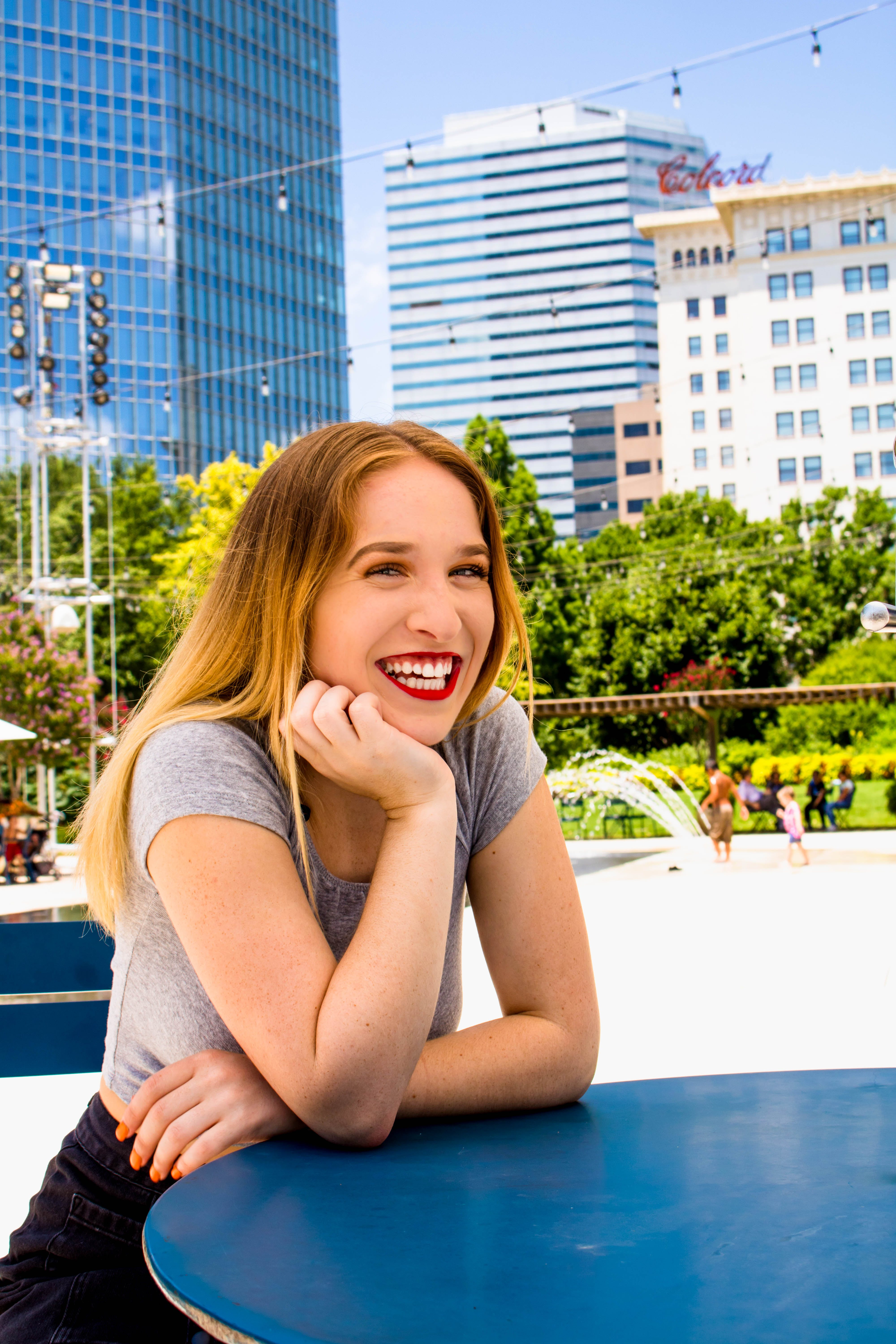 Woman Sitting in Front of Blue Table While Smiling on Camera