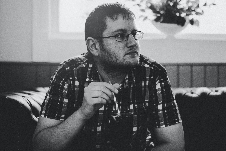 Grayscale Photo of Man Sitting on Sofa