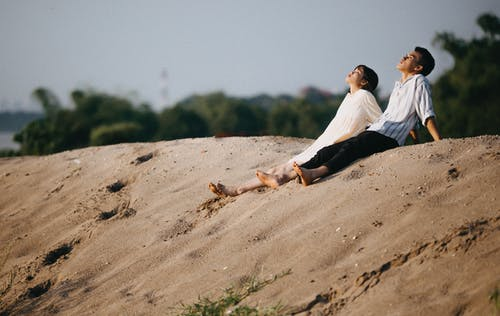 Man and Woman Sitting on the Sand