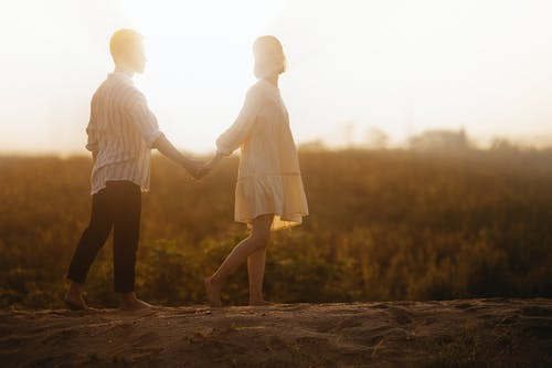 Couple Holding Hands on Sand Field