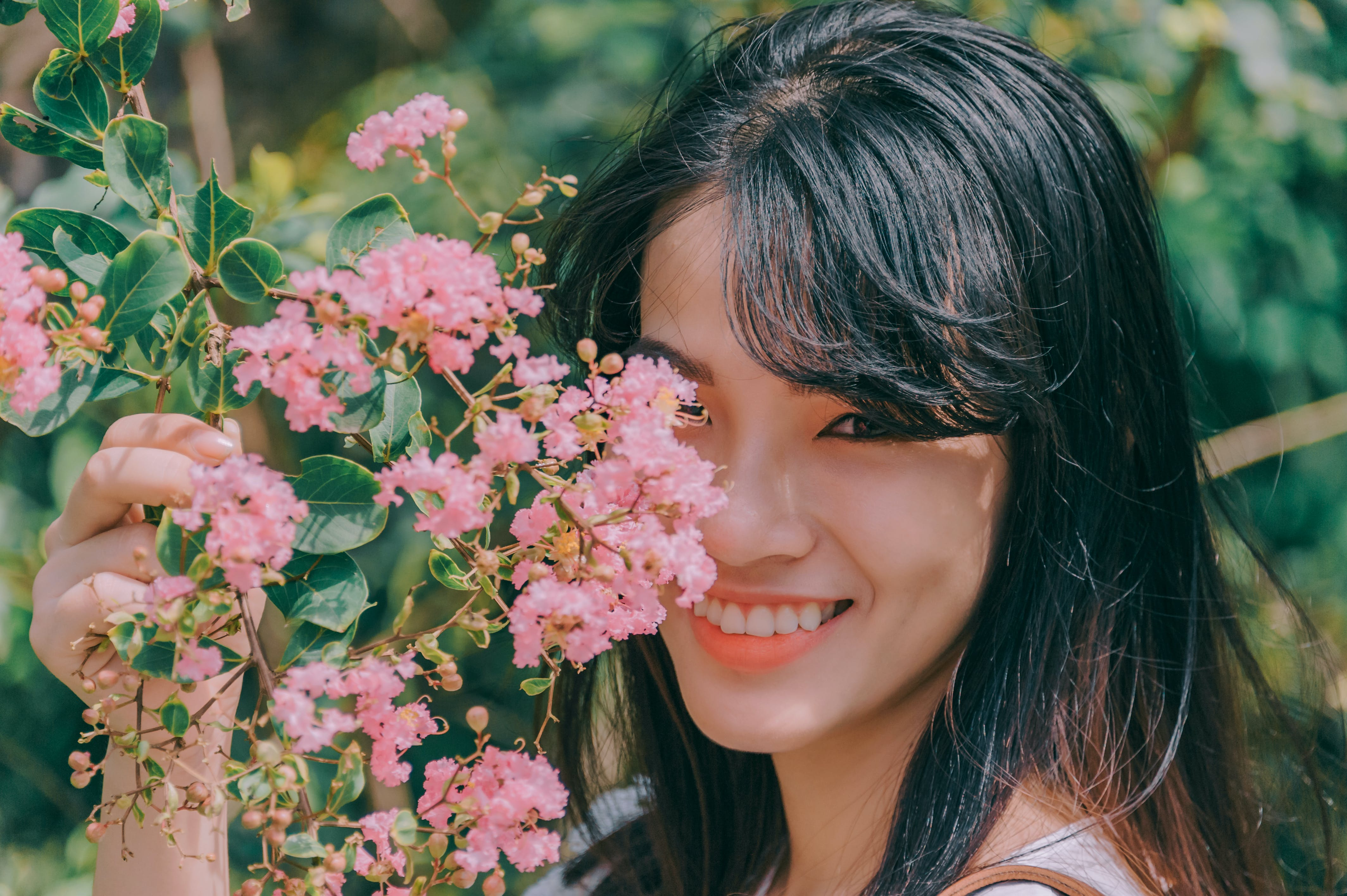 Black Haired Woman Smiling and Holding Pink Chestnut Flowers