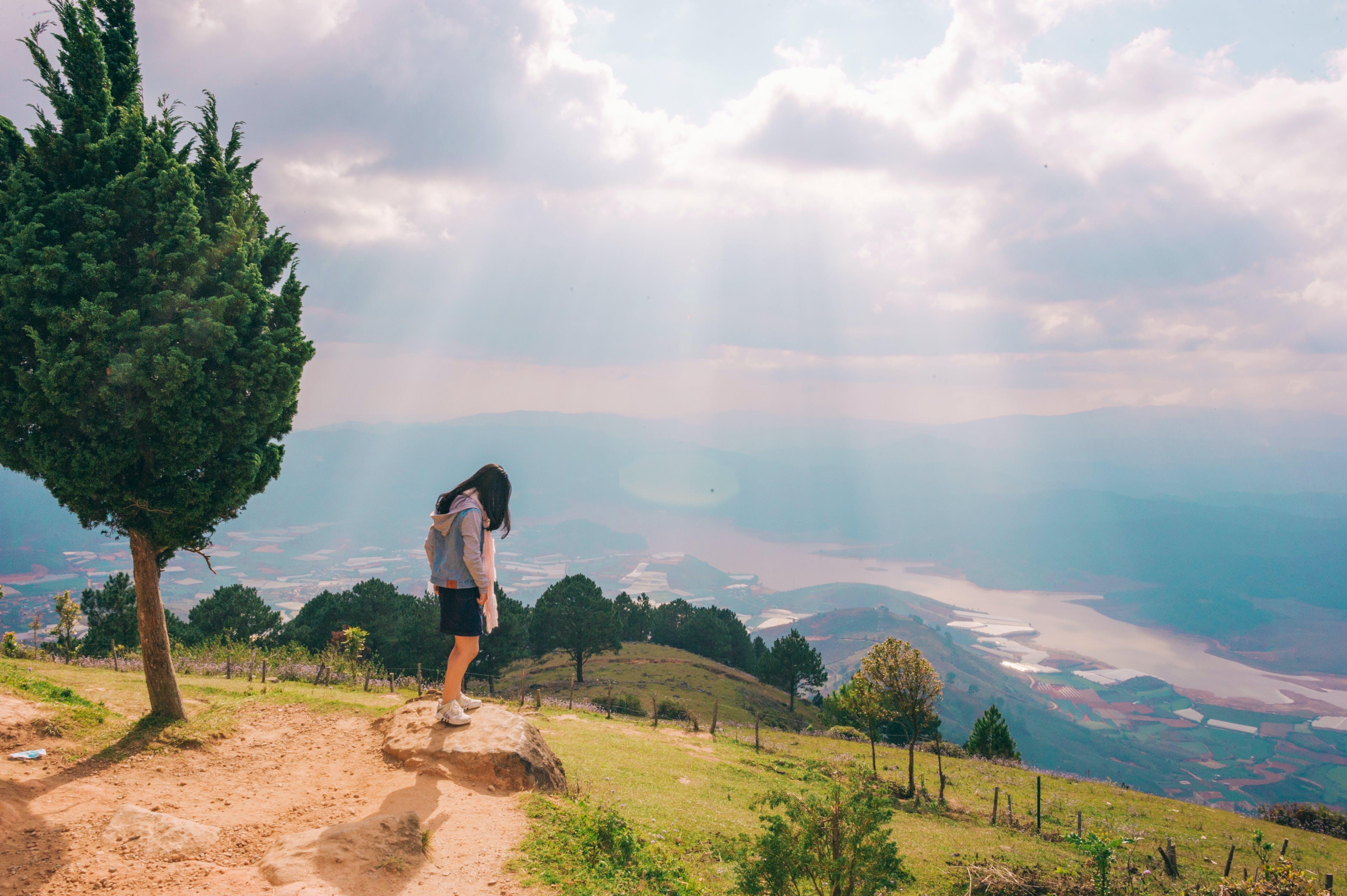 Woman Standing on Stone Near Tree