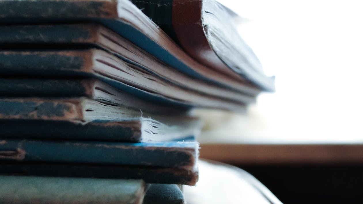 Piled Soft-bound Books on Table