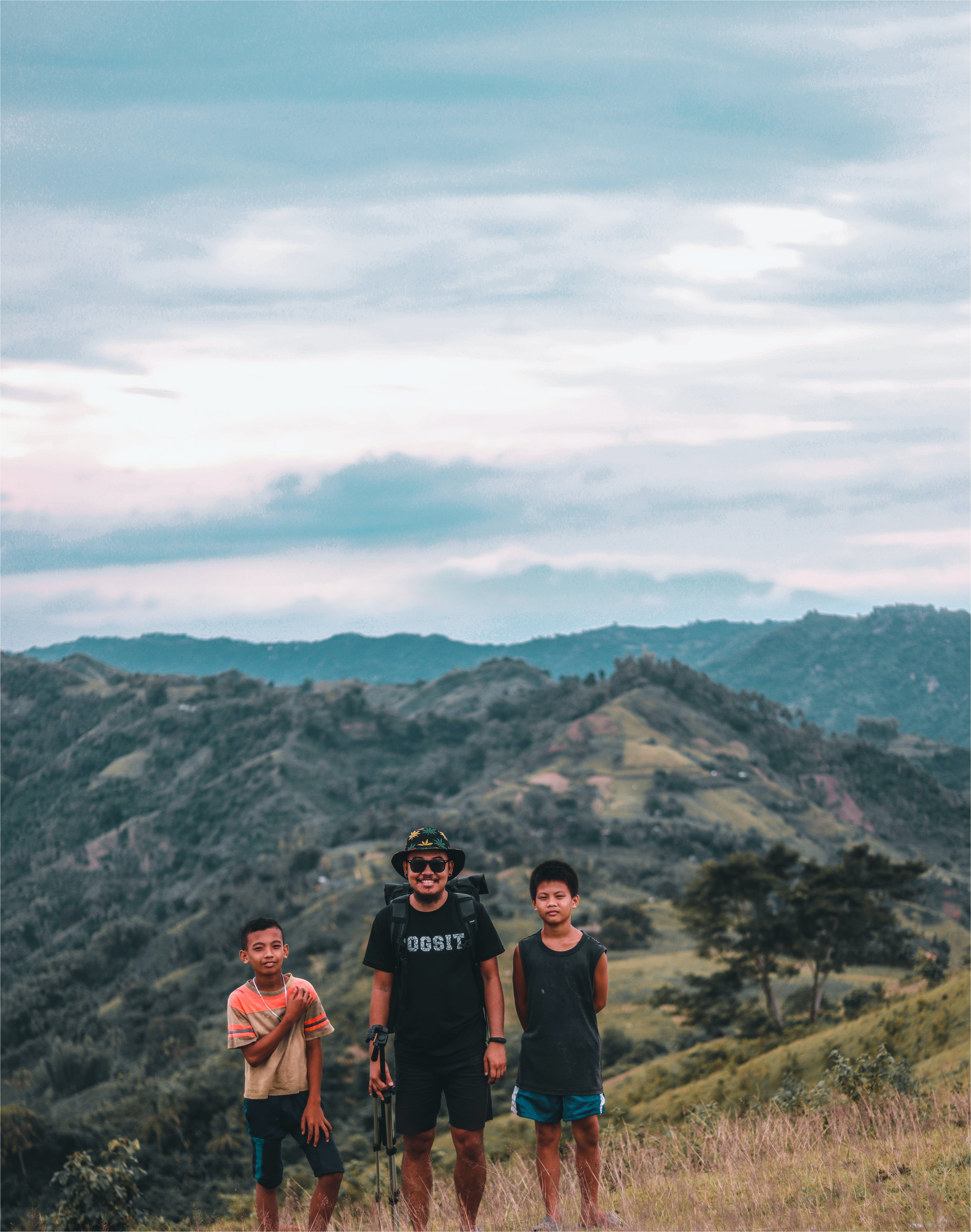Three Man Taking Photo With Mountains at Distance