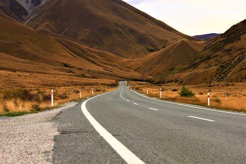 Gray Asphalt Road Between Brown Mountains