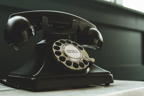 Black Rotary Telephone on White Surface