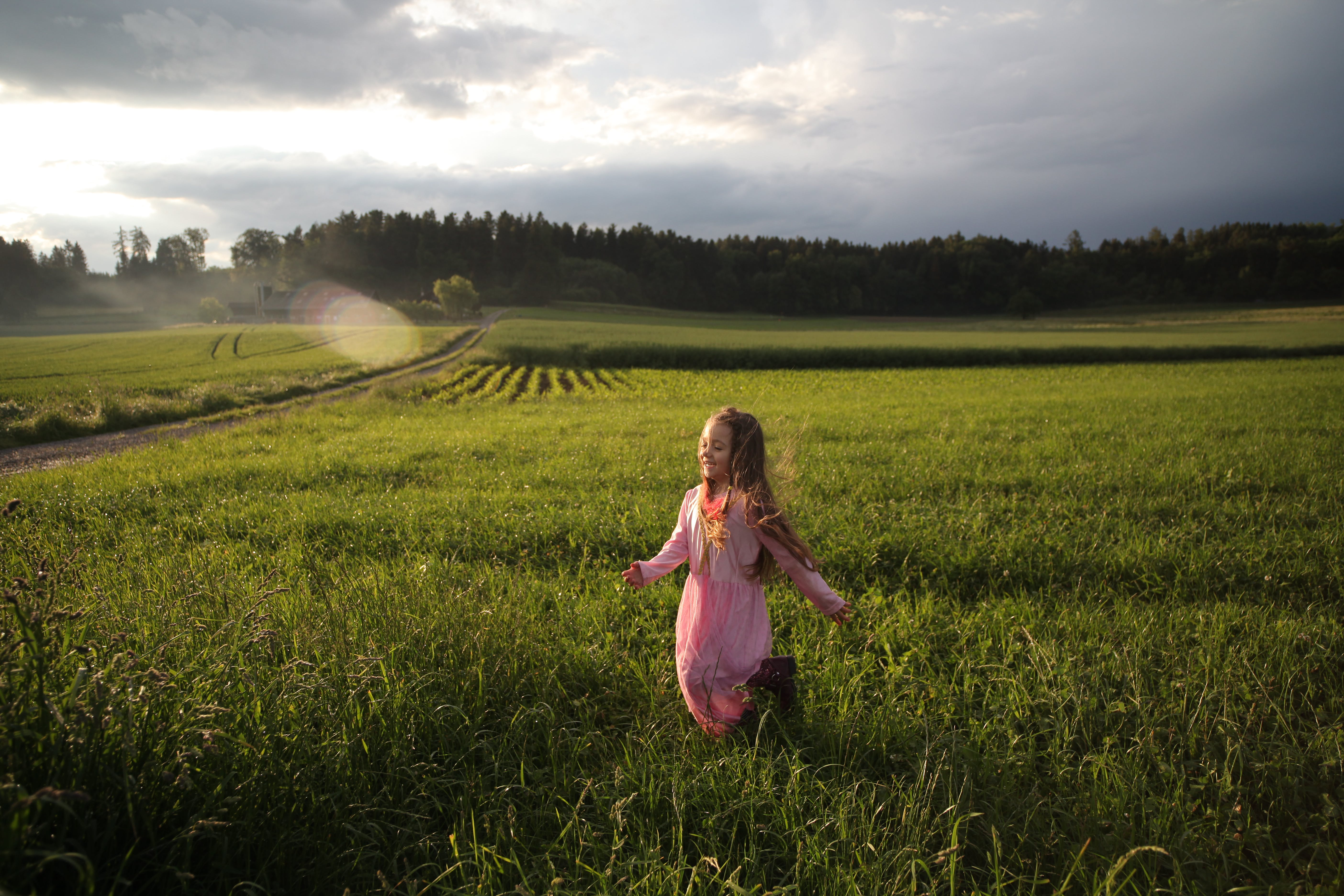 Girl Running on Green Grass Field Near Open Road