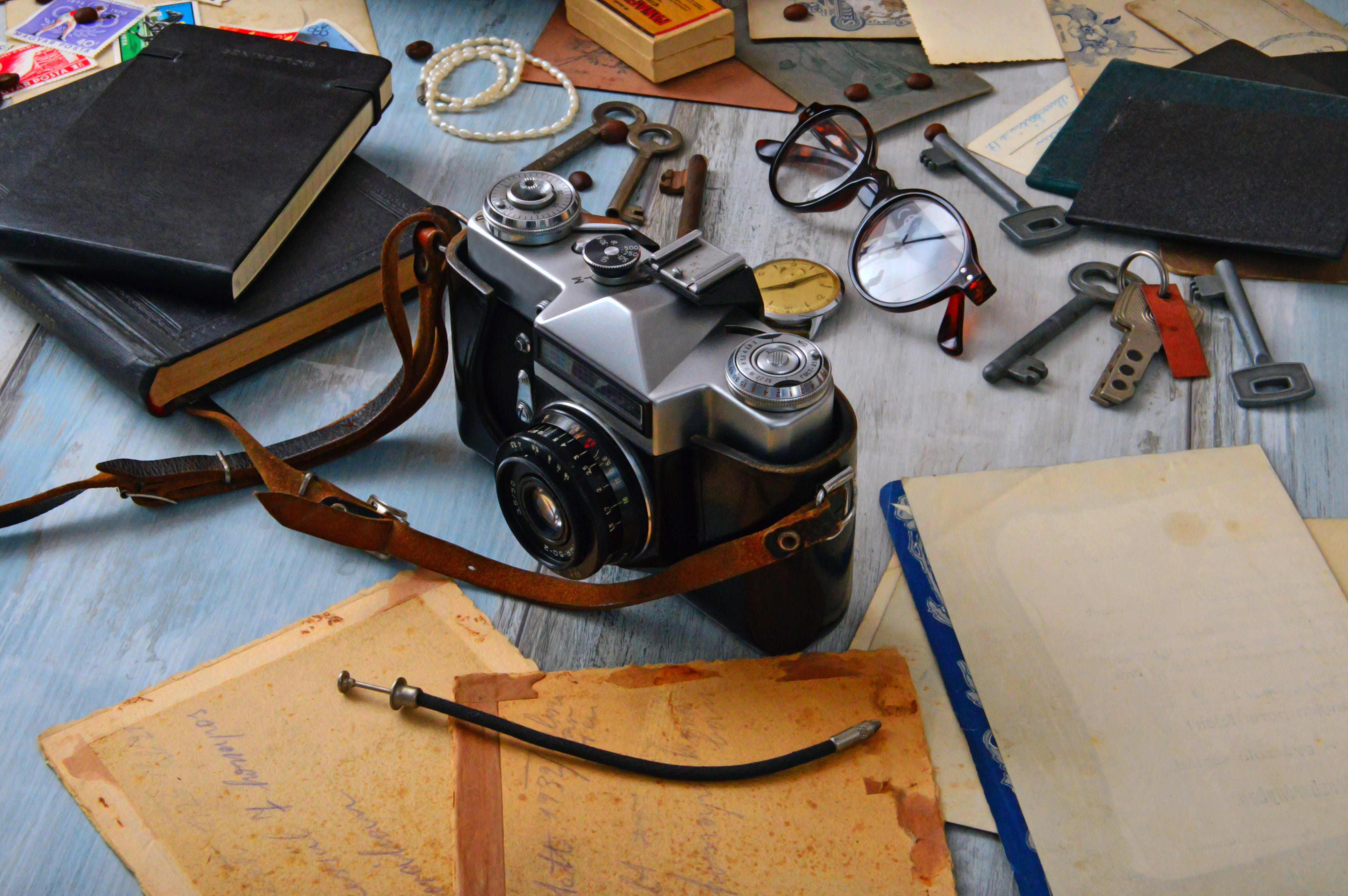 Black and Gray Camera on Table Surrounded by Books