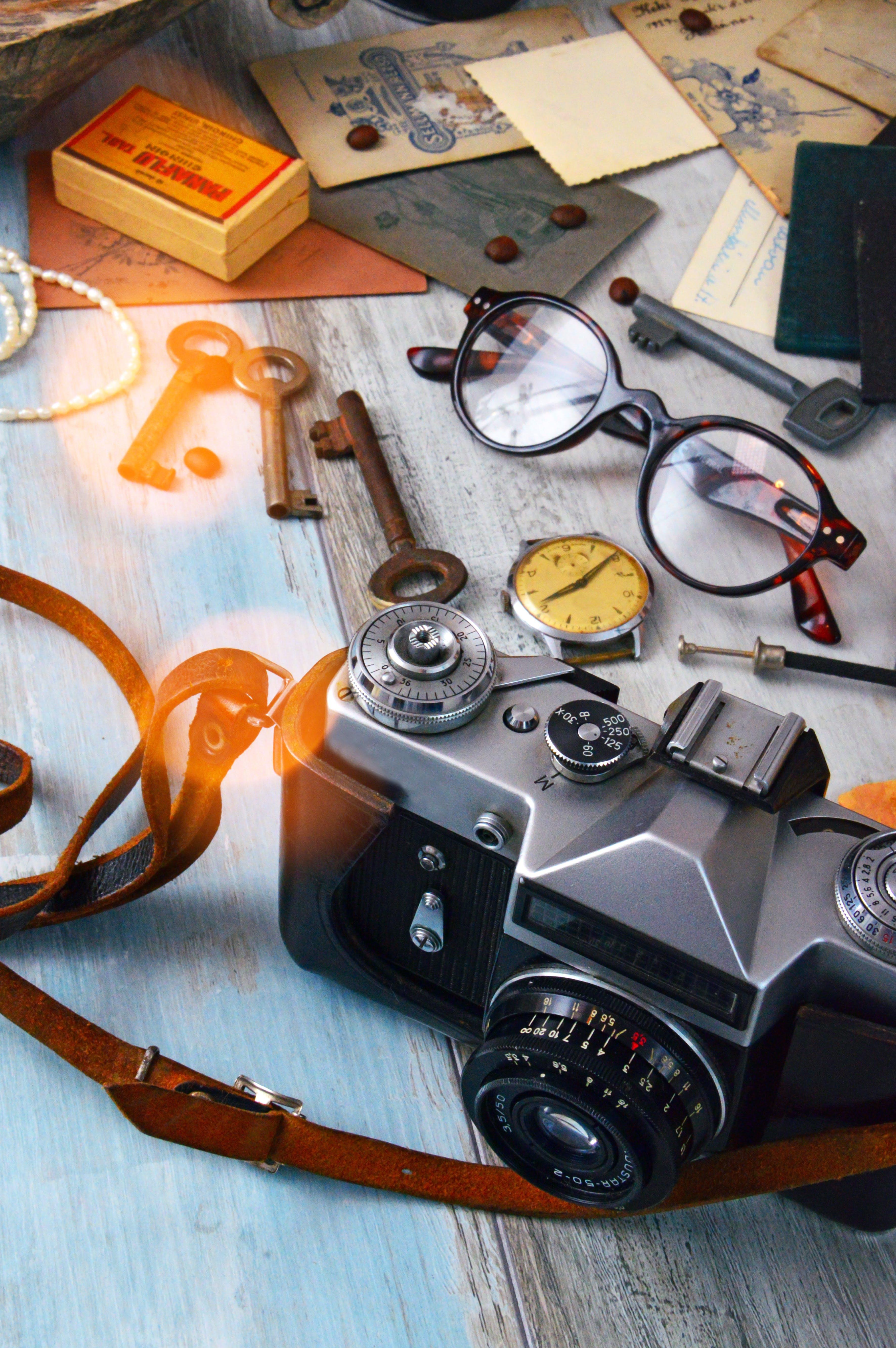 Black and Gray Camera, Skeleton Keys, and Brown Framed Eyeglasses on Gray Surface