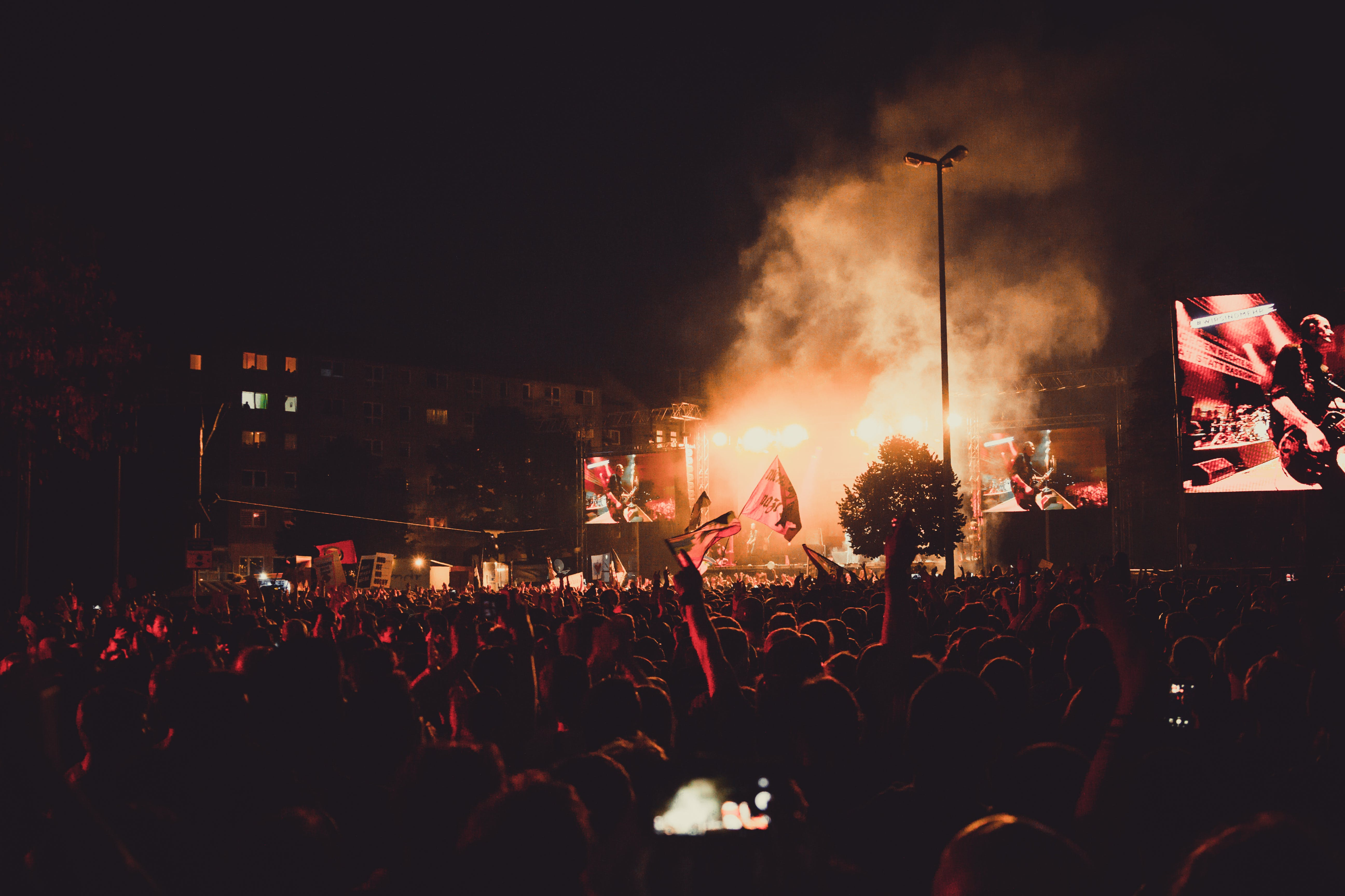 Band Performing on Smoky Stage in Front of People during Night Time